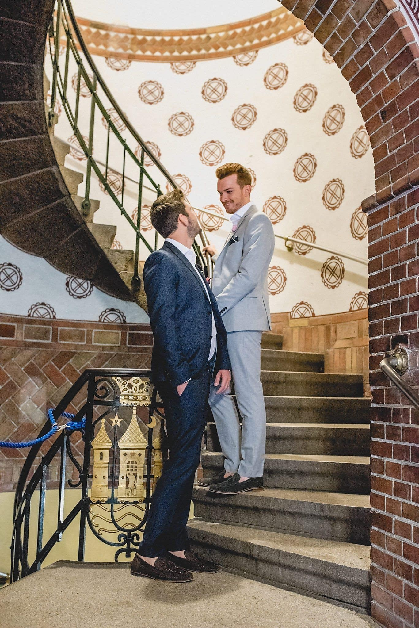 Gay grooms on the spiral staircase of the Copenhagen Radhus before their wedding ceremony