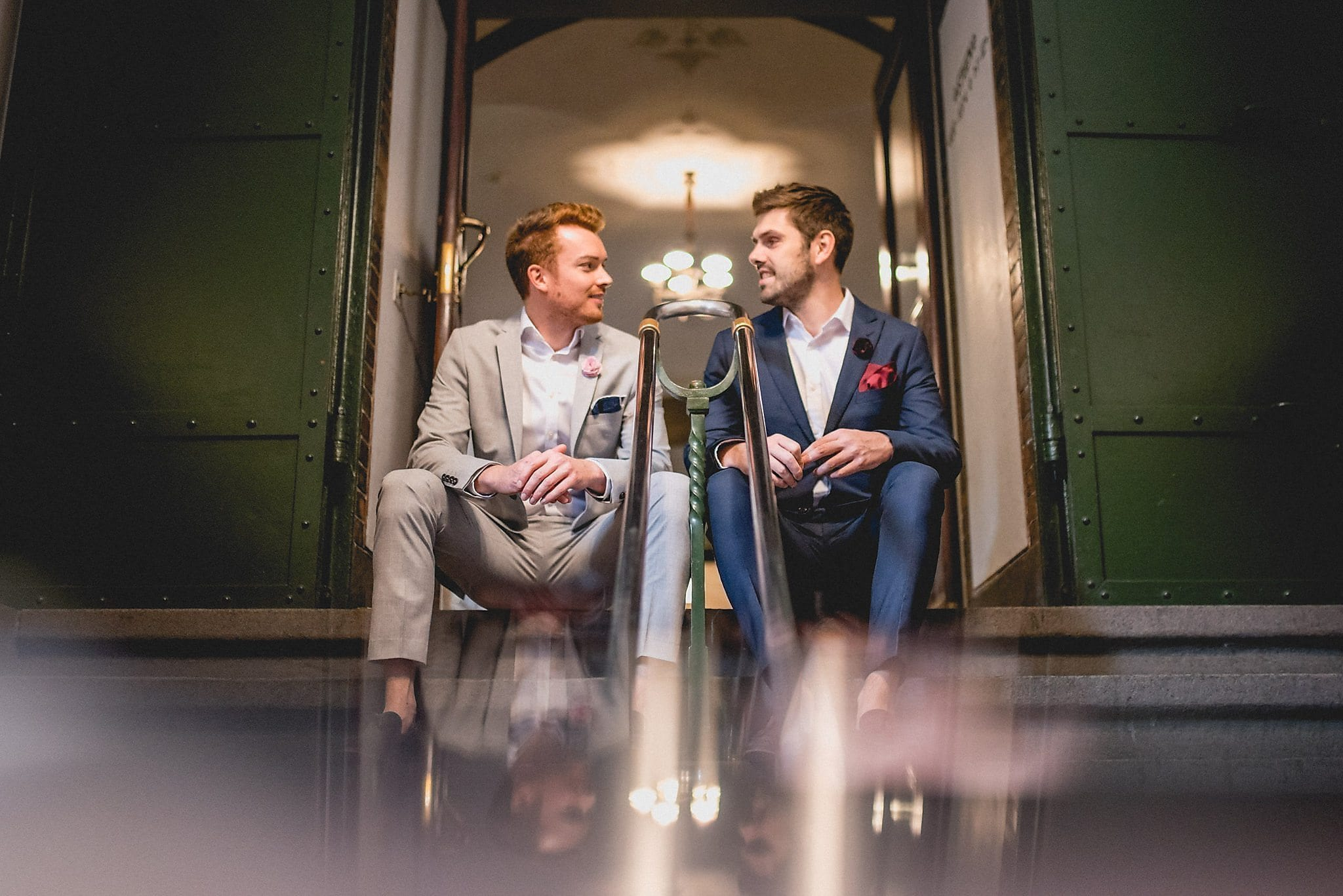 Same-sex couple sits on the steps of the Copenhagen Rådhus before their wedding ceremony