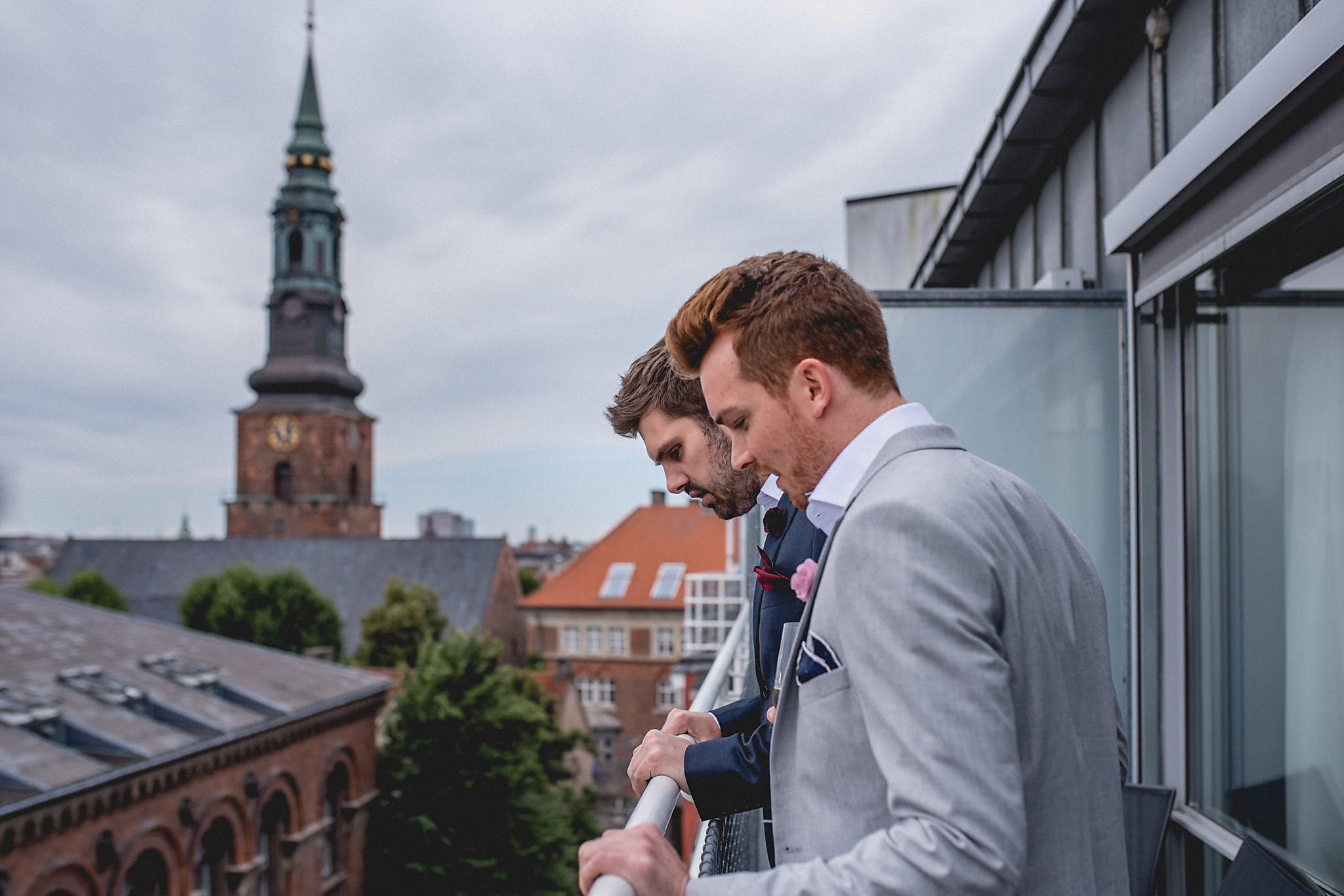 Drew and Tom stand on the balcony of their hotel looking out over Copenhagen