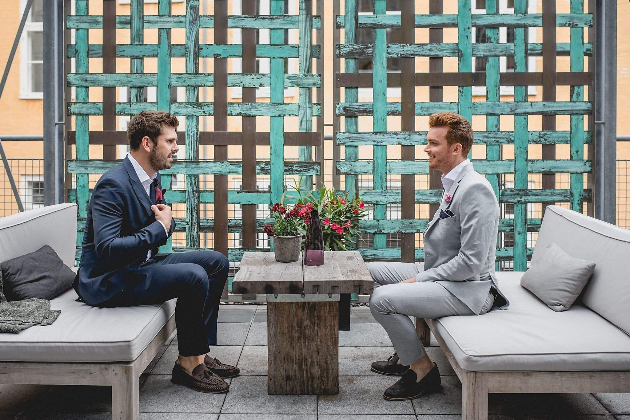 Drew and Tom are seated opposite one another in front of a teal trellis on the roof of their stylish Copenhagen hotel