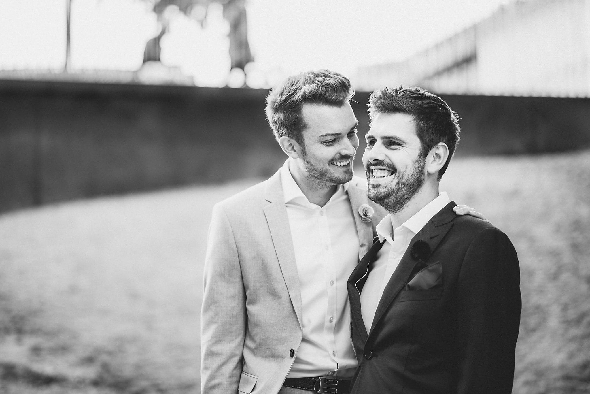 Two grooms laugh together at their Copenhagen Destination Wedding