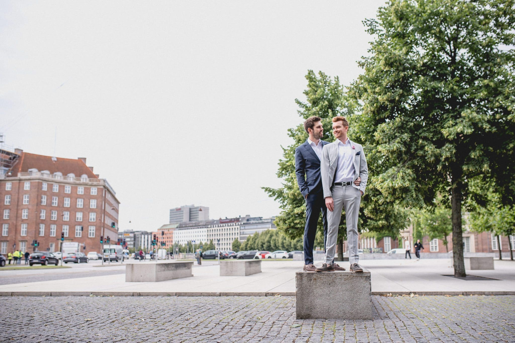 A striking same-sex couple standing together on a pillar in a Copenhagen square