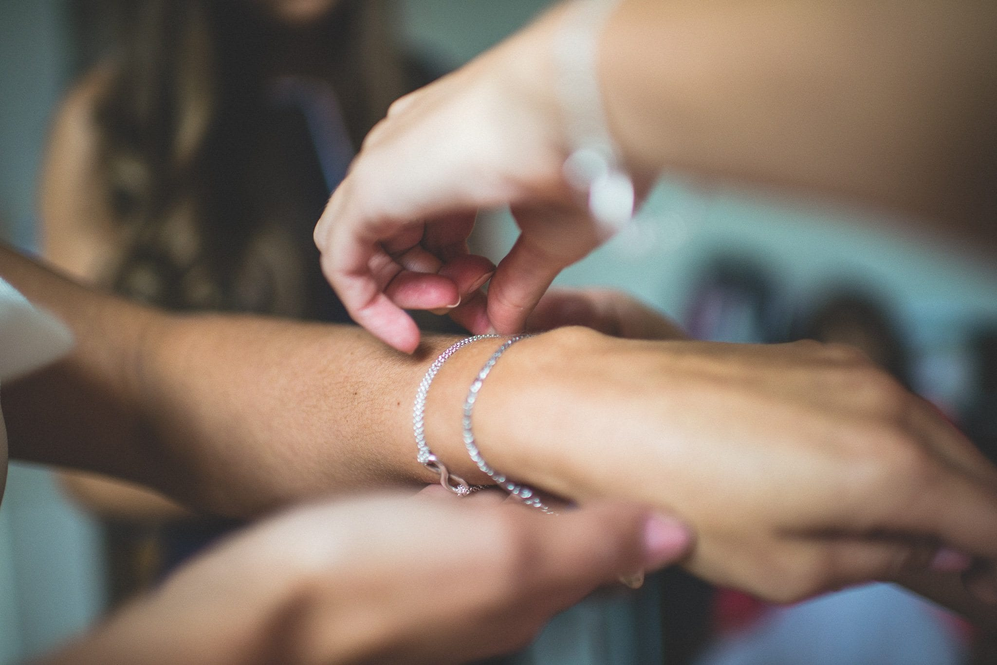 Ilaria's bridesmaids fasten delicate silver bracelets around her wrist as she gets ready