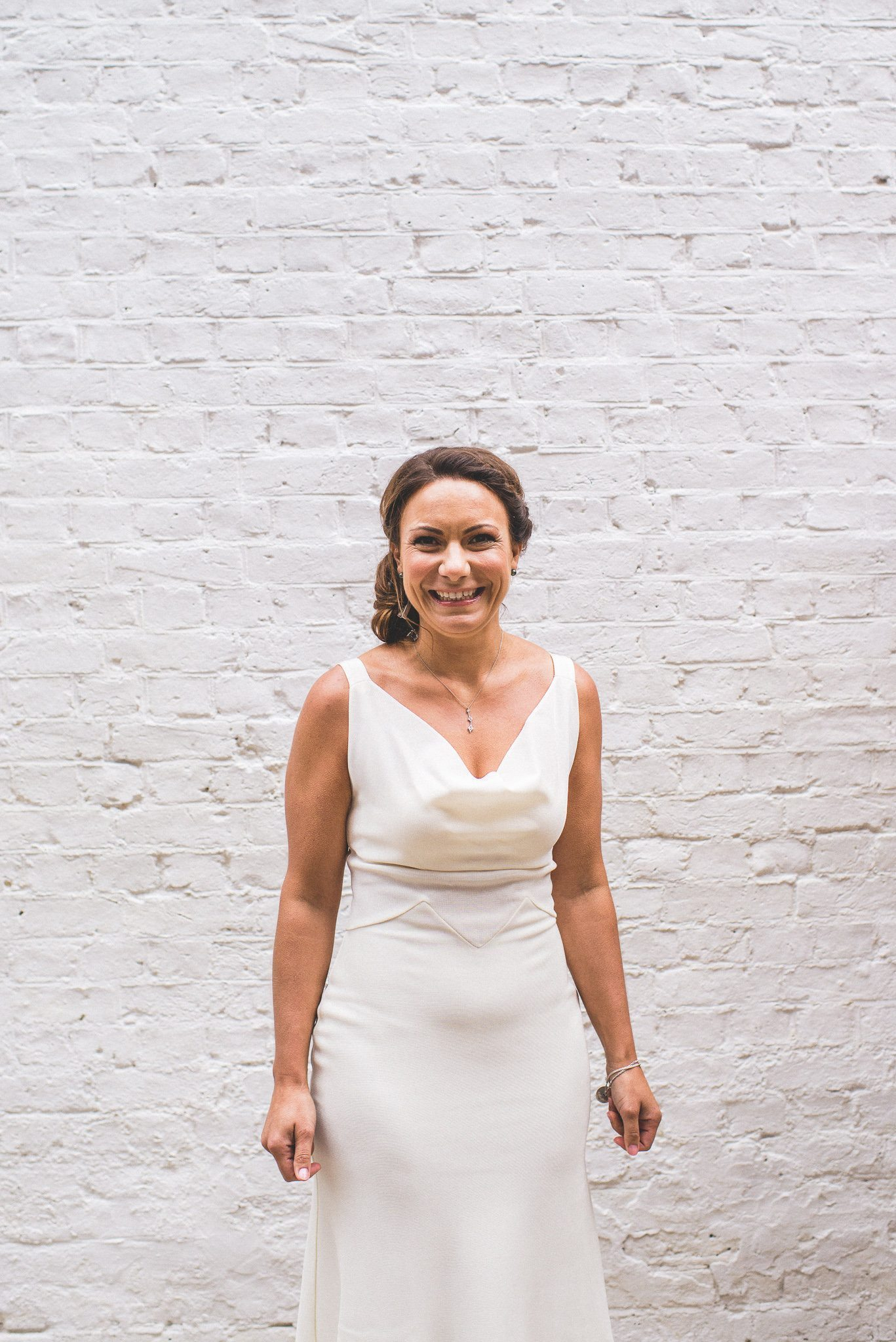 Ilaria shows off her finished bridal look in a simple Dior gown, pendant and loose up-do as she stands in front of a white brick wall
