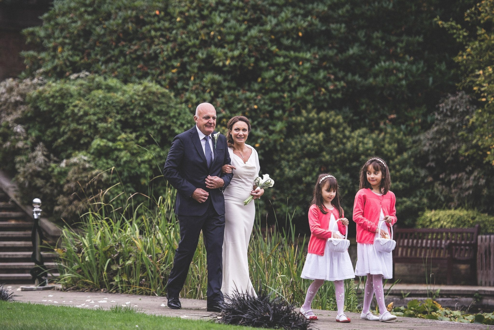 The bride and her father cross to the Pergola, preceded by two flower girls in white dresses and red cardigans, carrying baskets of petals