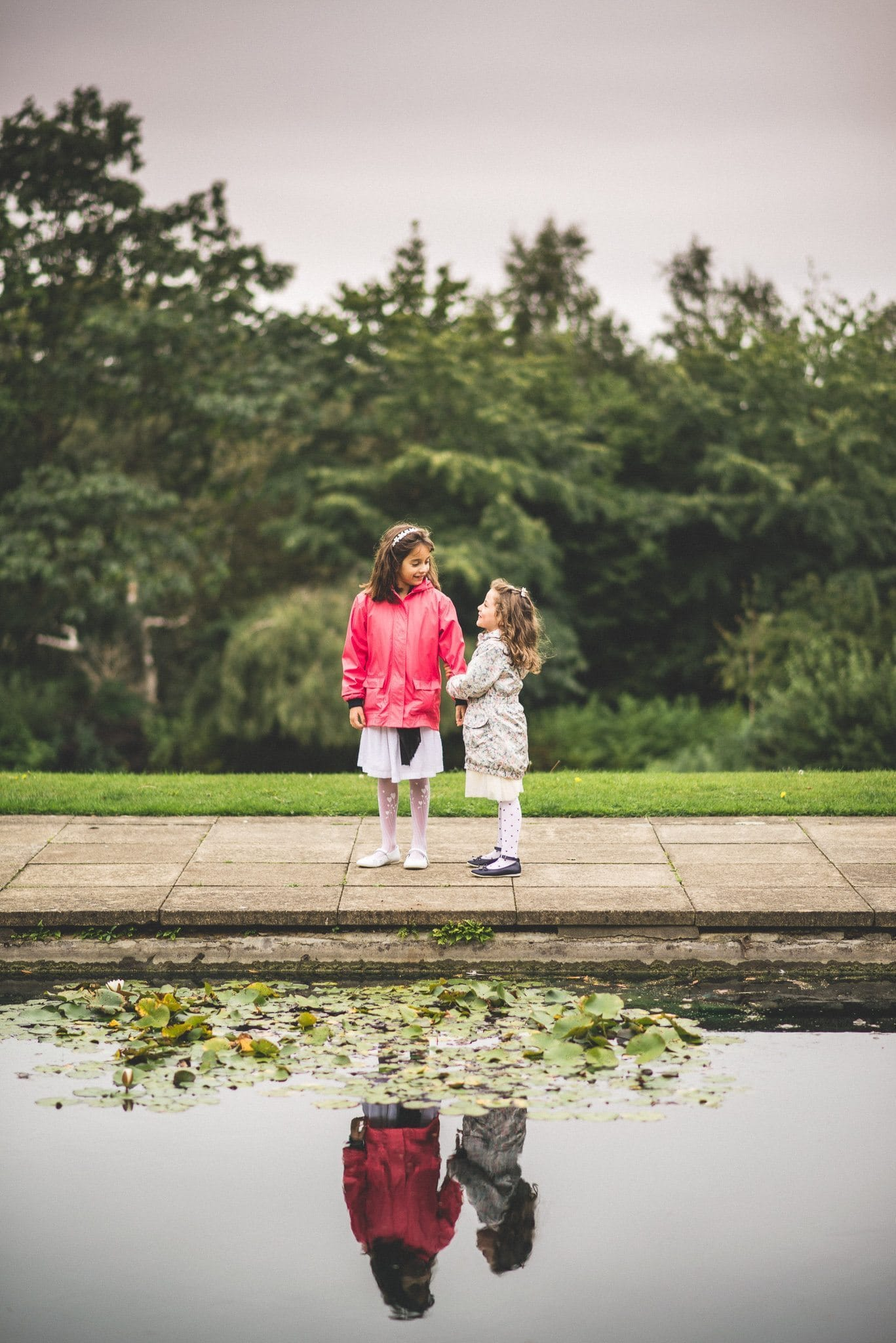 The flower girls hold hands standing at the edge of an ornamental pond