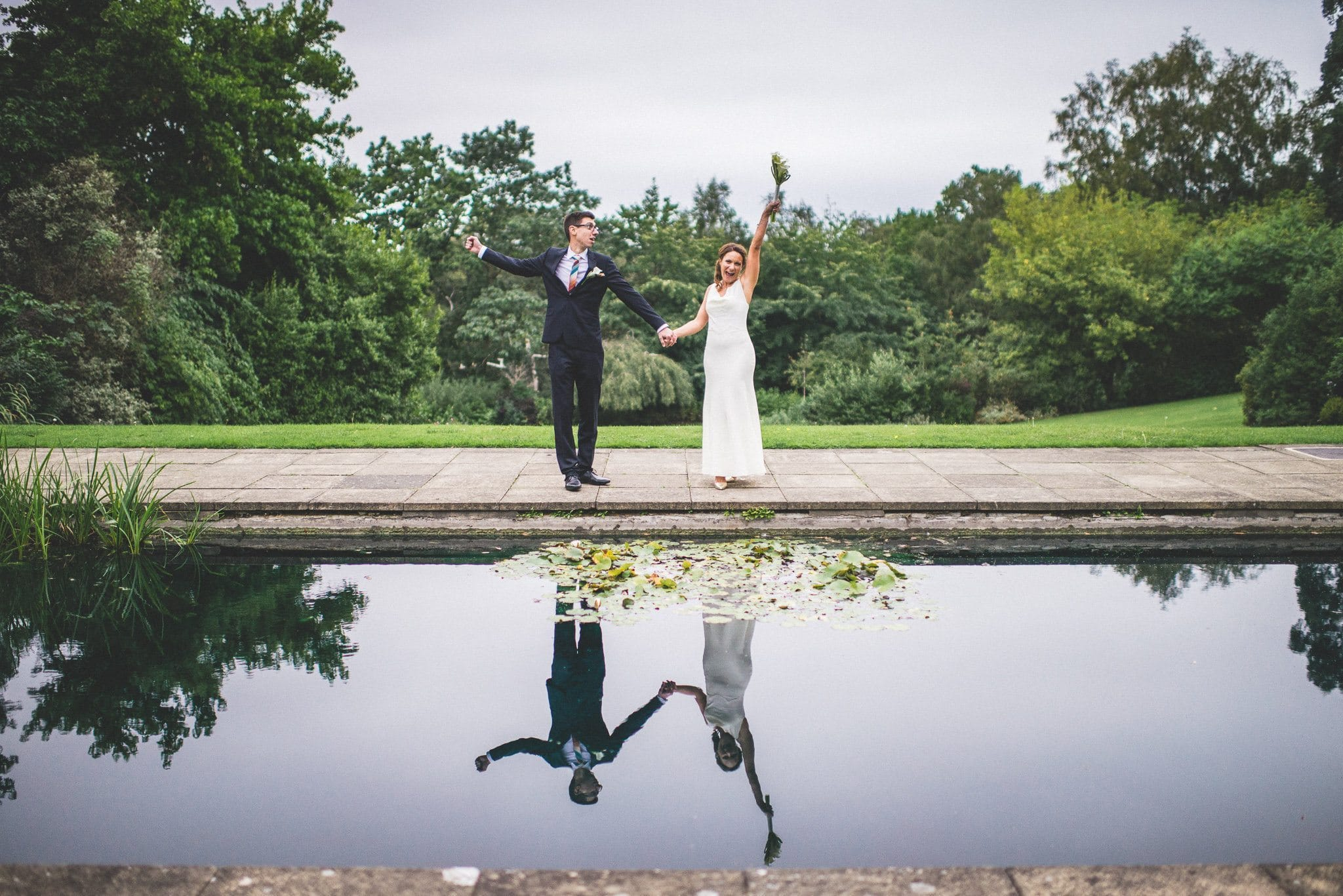 That 'just married' feeling! Marco and Ilaria punch the air with excitement at the edge of the ornamental pond