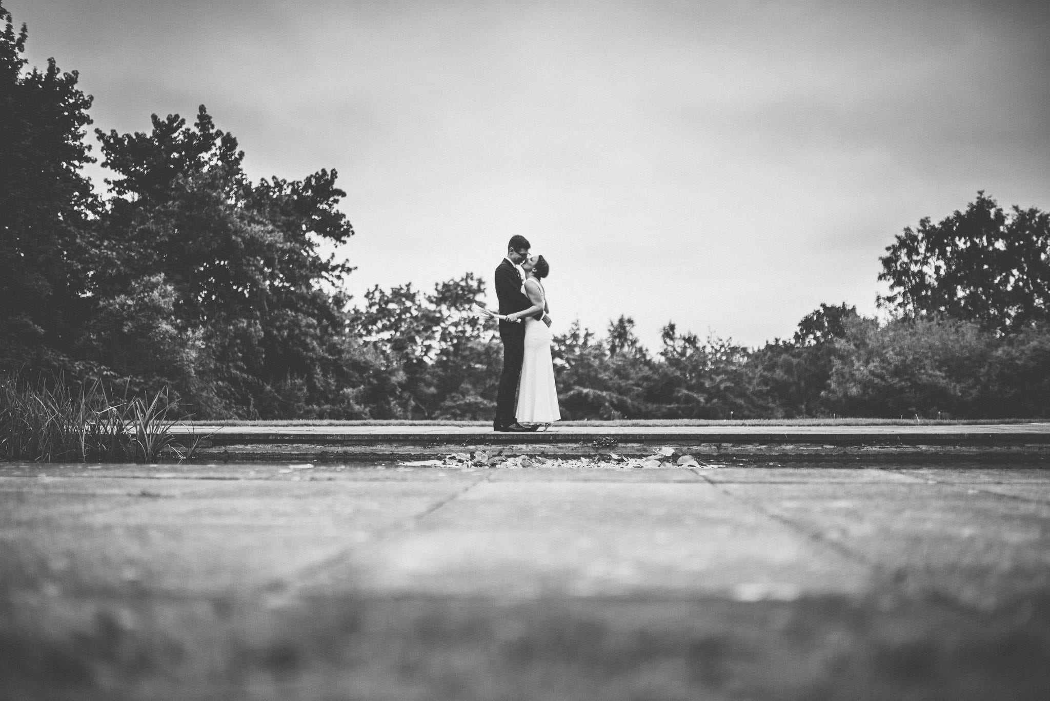A black and white shot of the newlyweds kissing by the pond