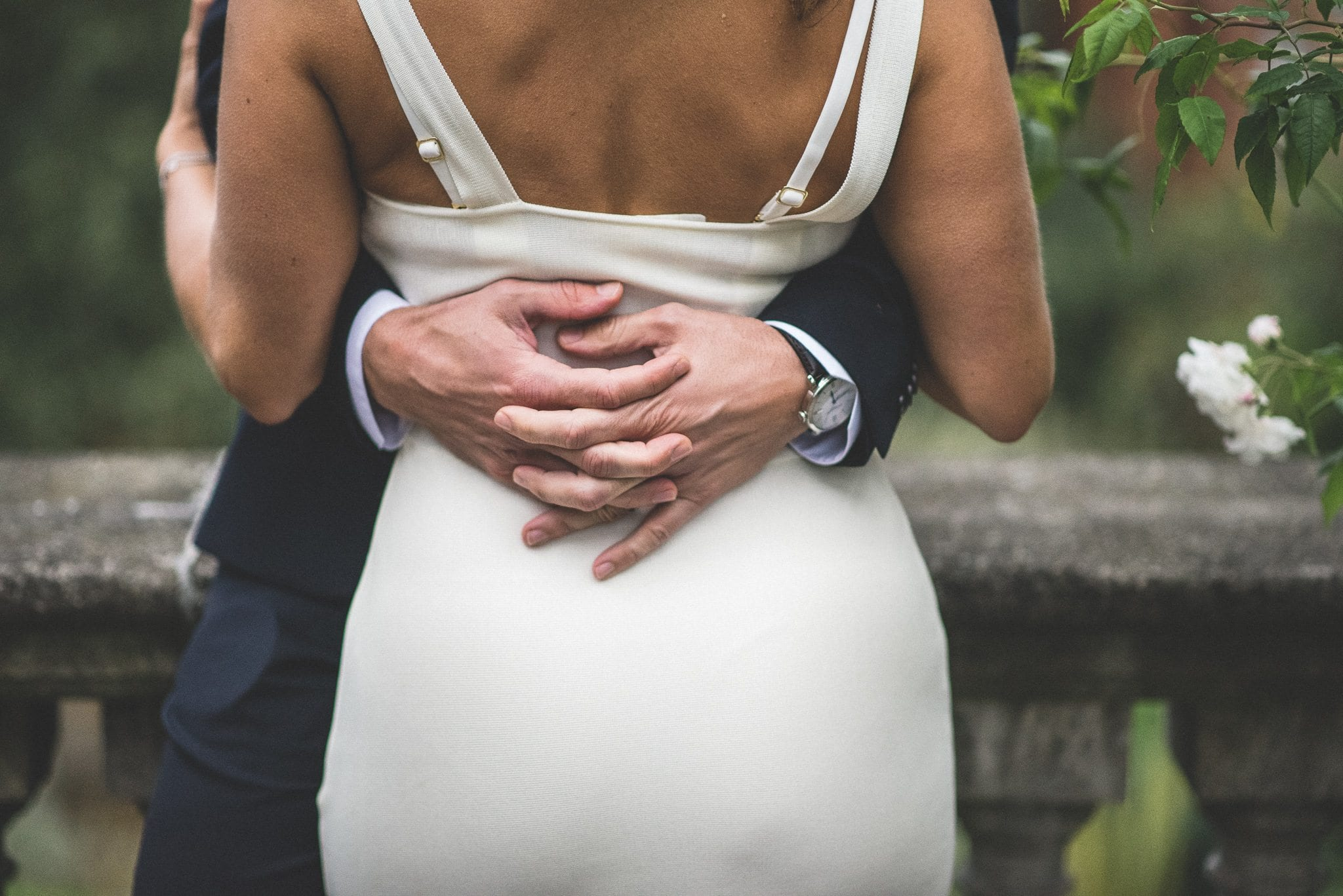 Groom holding the bride in his arms and interlacing his fingers at the back of her waist at the Hampstead Pergola