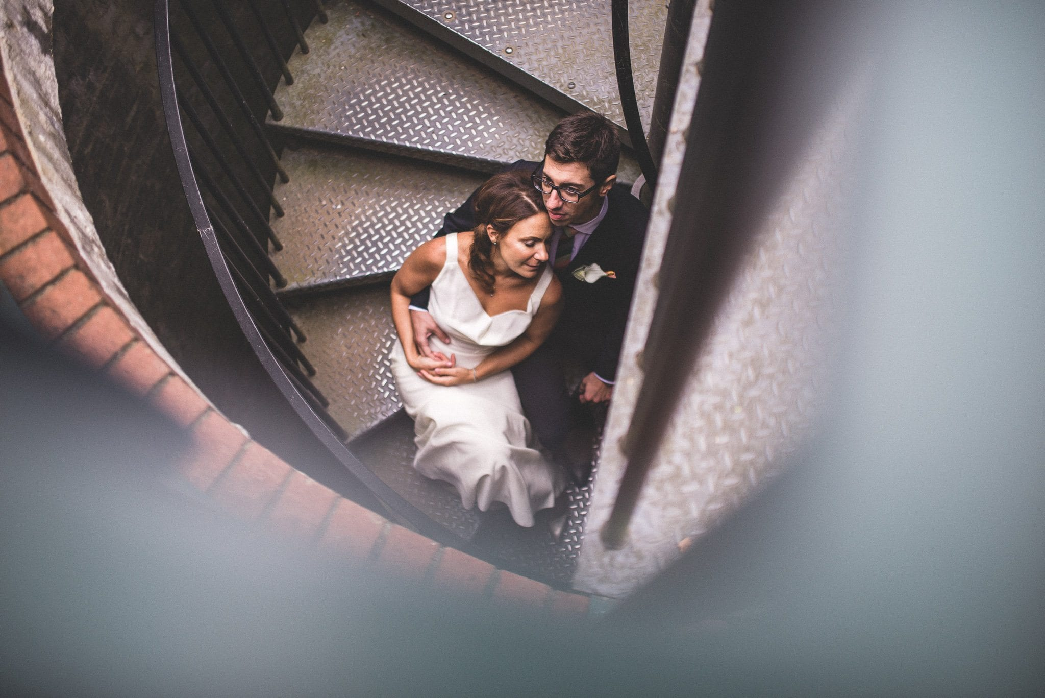 A shot from above. Marco holds his new bride tenderly as the couple sit on a spiral staircase