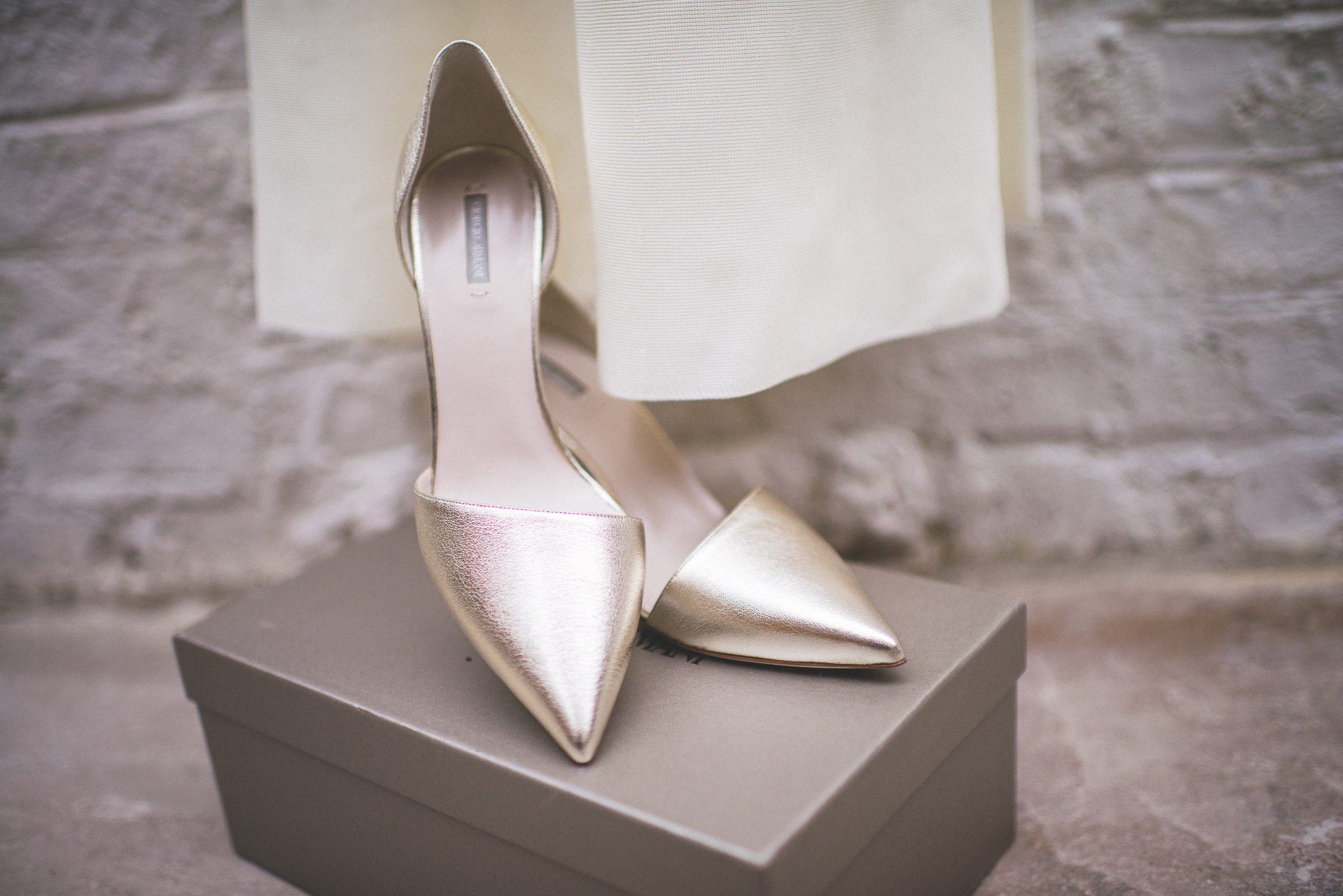 A close up of Ilaria's gold Armani stiletto heels
