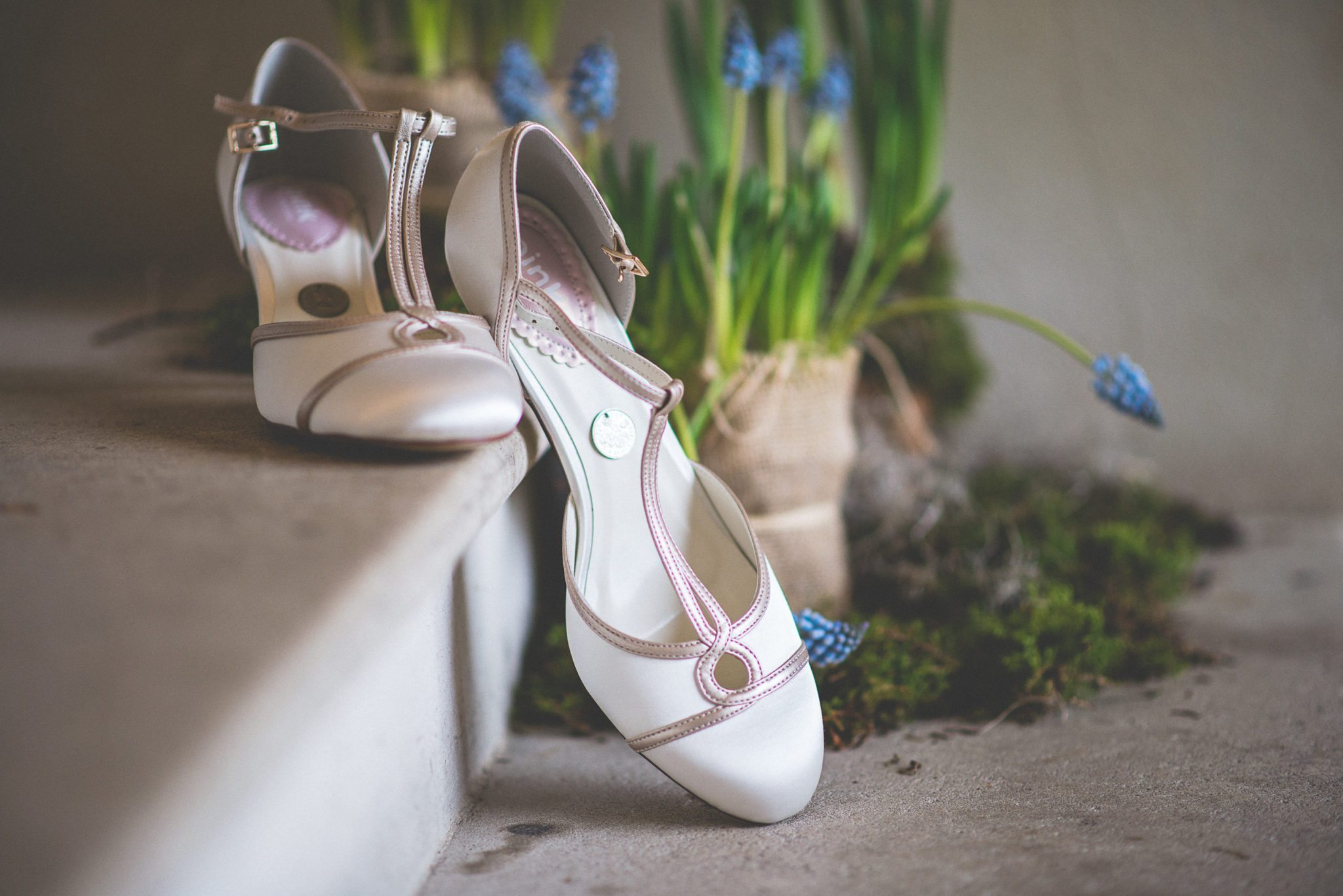 The bride's white shoes, complete with lucky sixpence, sit on a stone step with a pot of grape hyacinth in the background