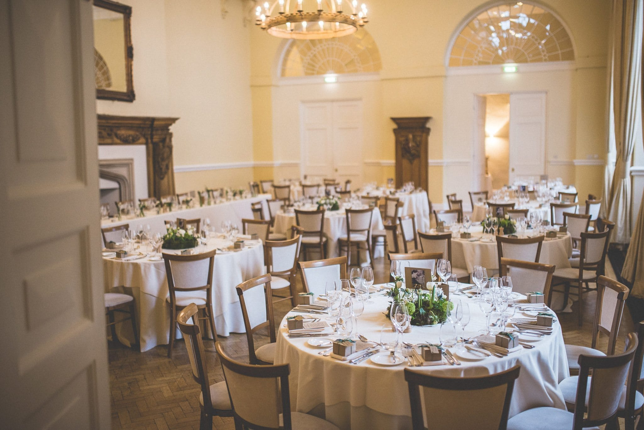A shot through the door of the reception venue showing tables decorated with spring flowers and favours