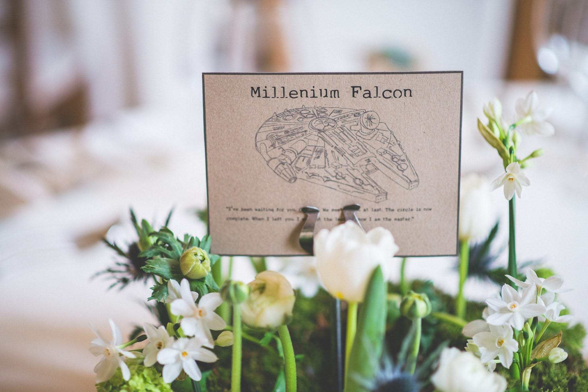 A close up of one of the table centres, showing the Millenium Falcon printed on rustic card among white flowers.