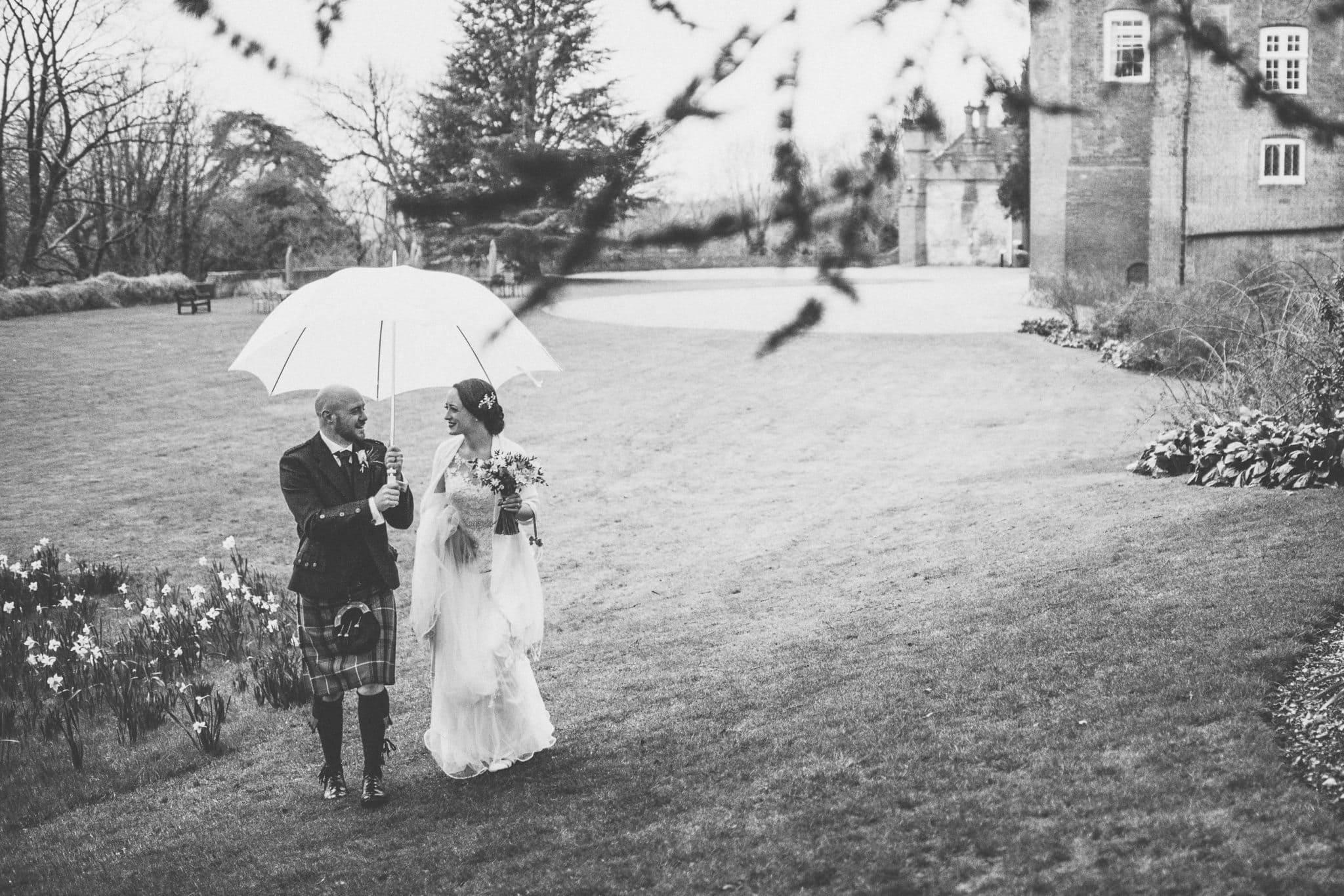 Bride and groom walking through Farnham Castle grounds at their rainy wedding
