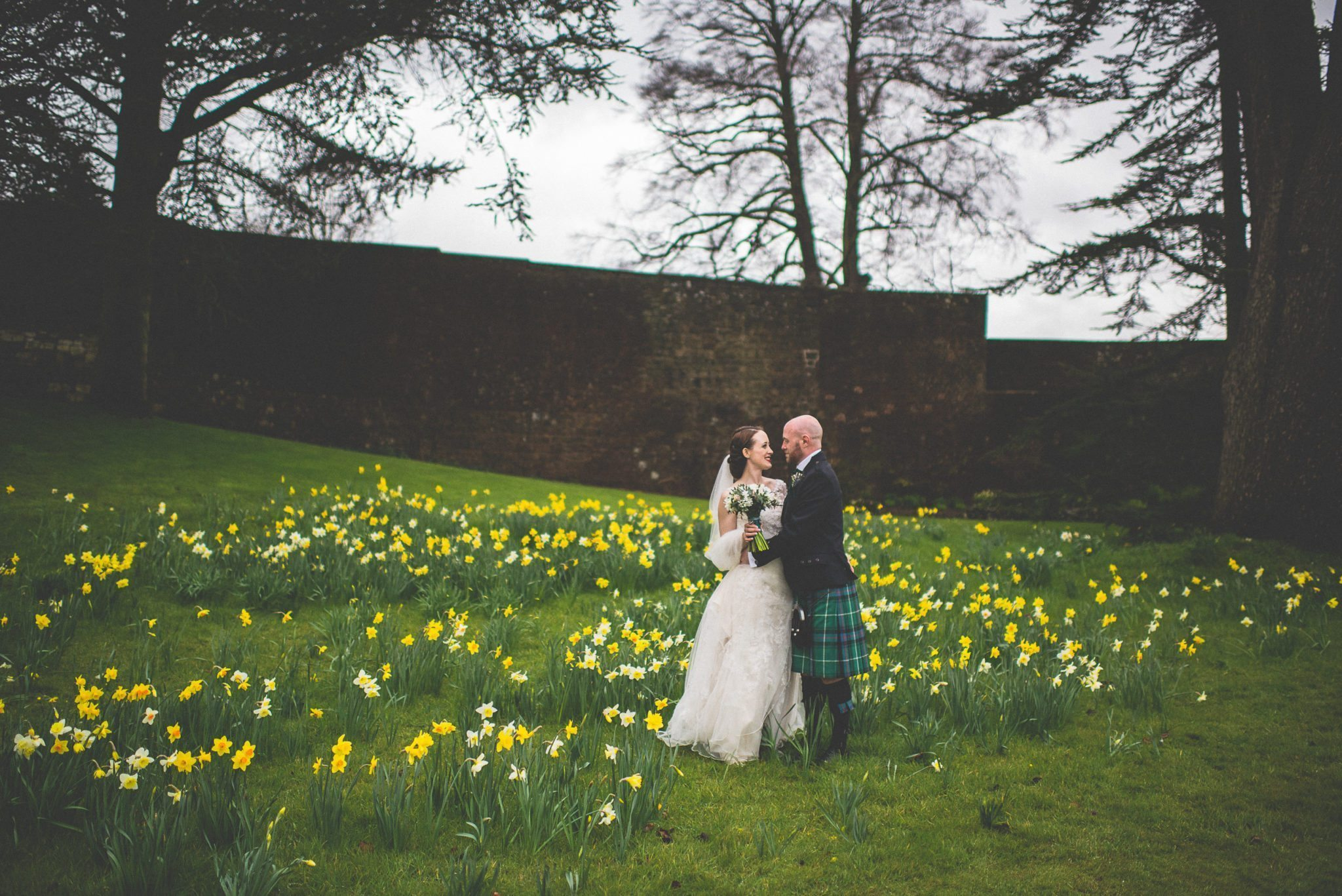 The couple stand amid a patch of daffodils in the grounds of Farnham Castle