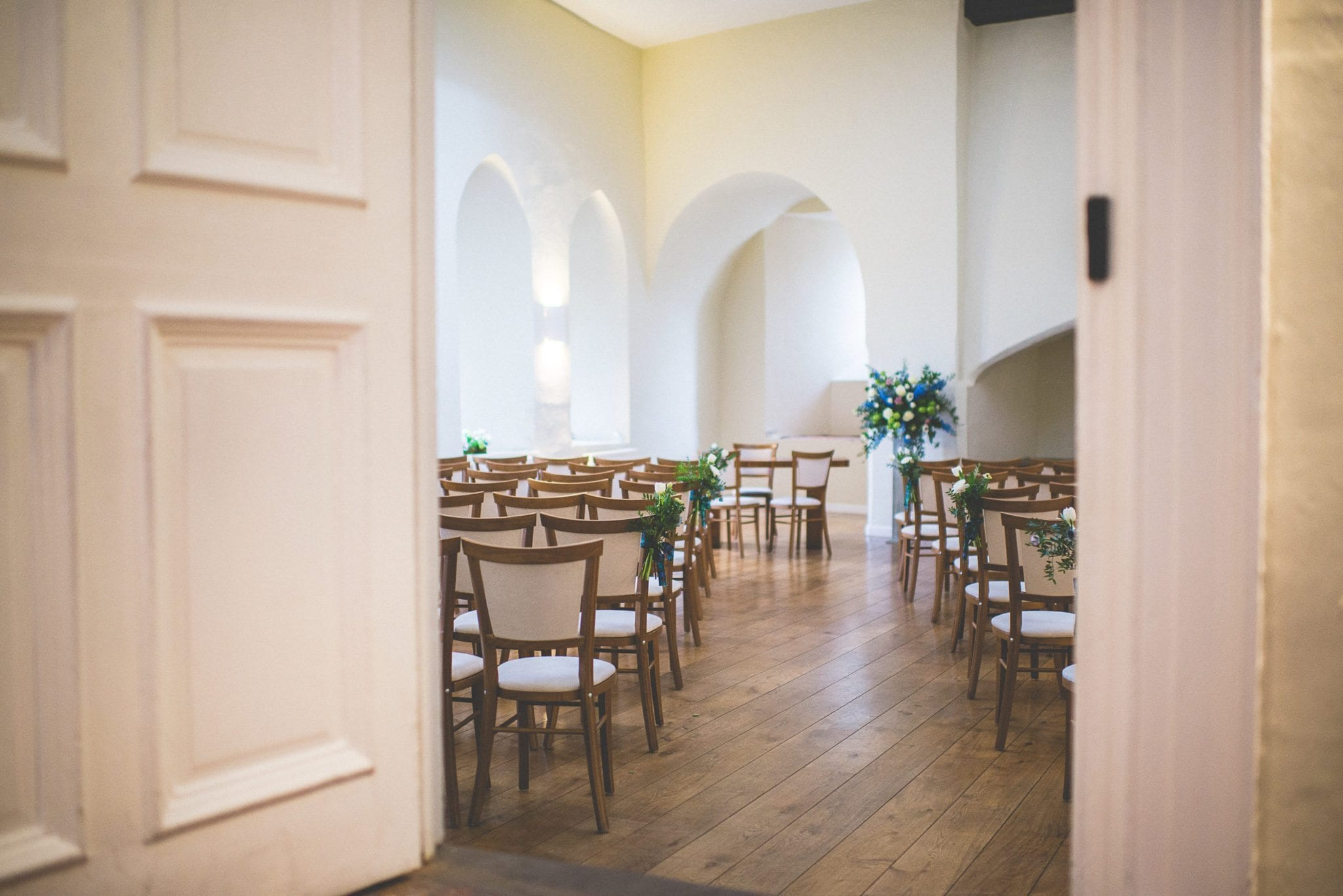 A peek through the door to the ceremony venue - Farnham Castle gatehouse - decorated with wooden chairs and simple floral arrangements