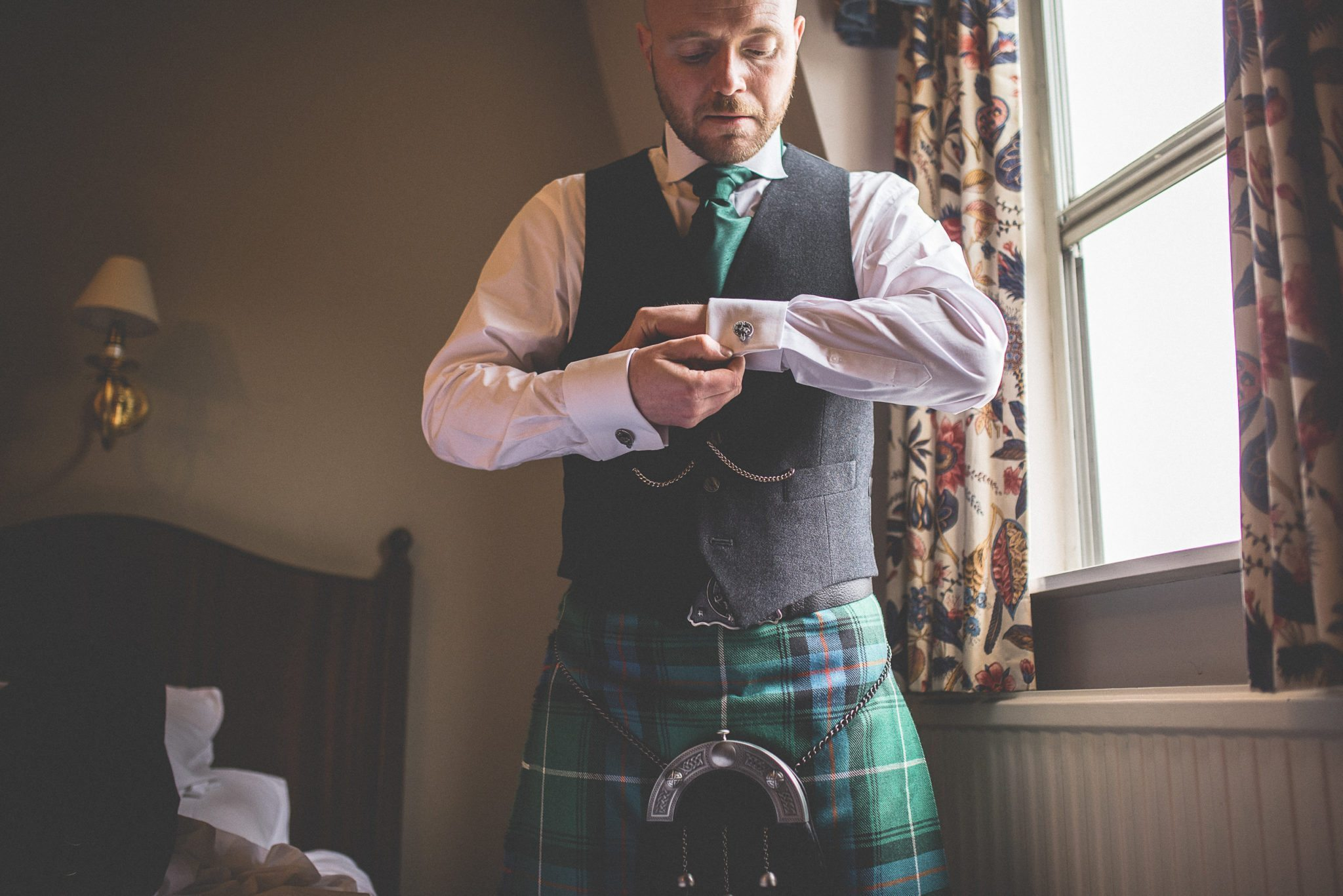 Groom Andy puts the final touches to his outfit, including green and black tartan kilt, green tie and cufflinks