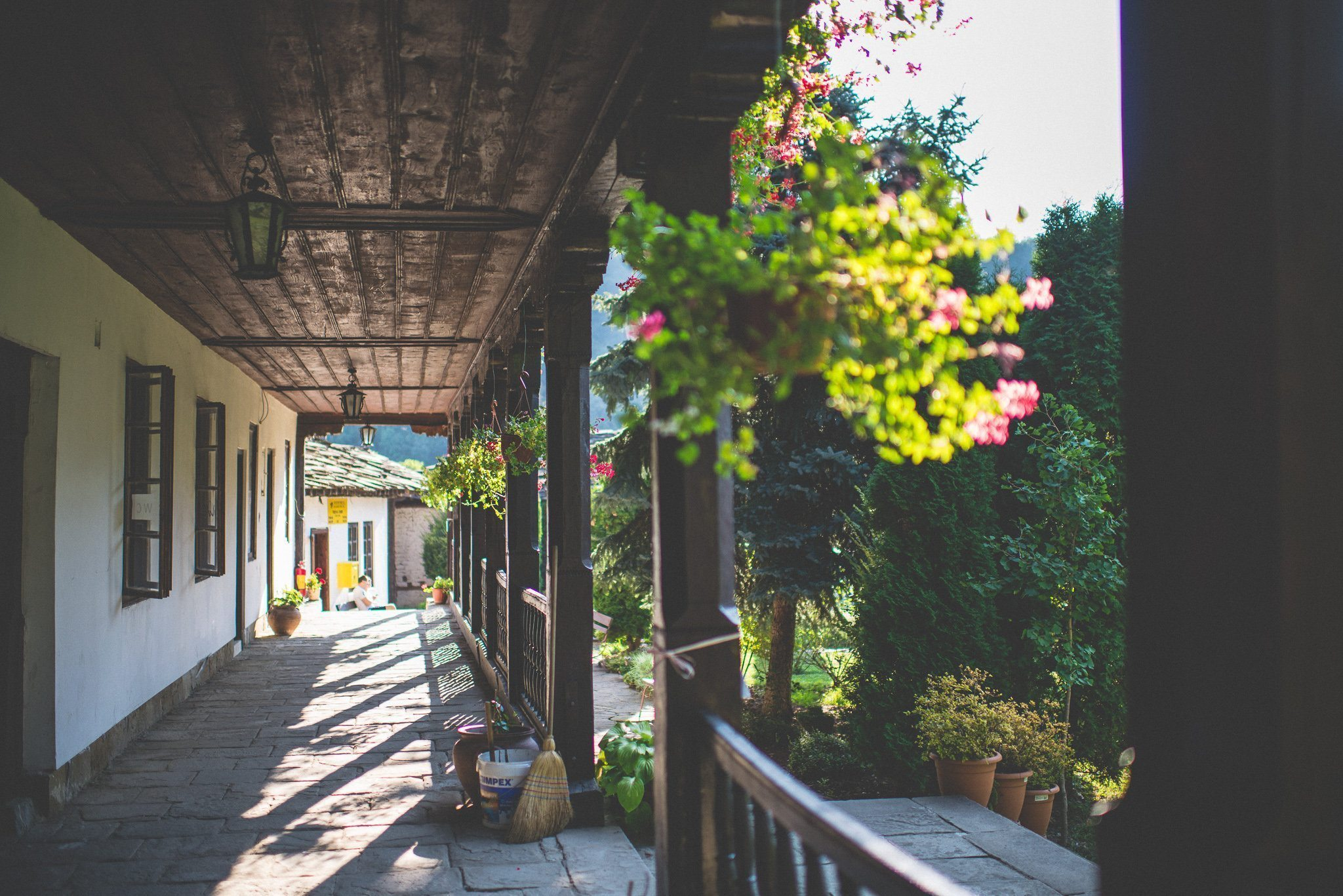 Baskets of flowers hang along the wooden verandah of the Troyan monastery
