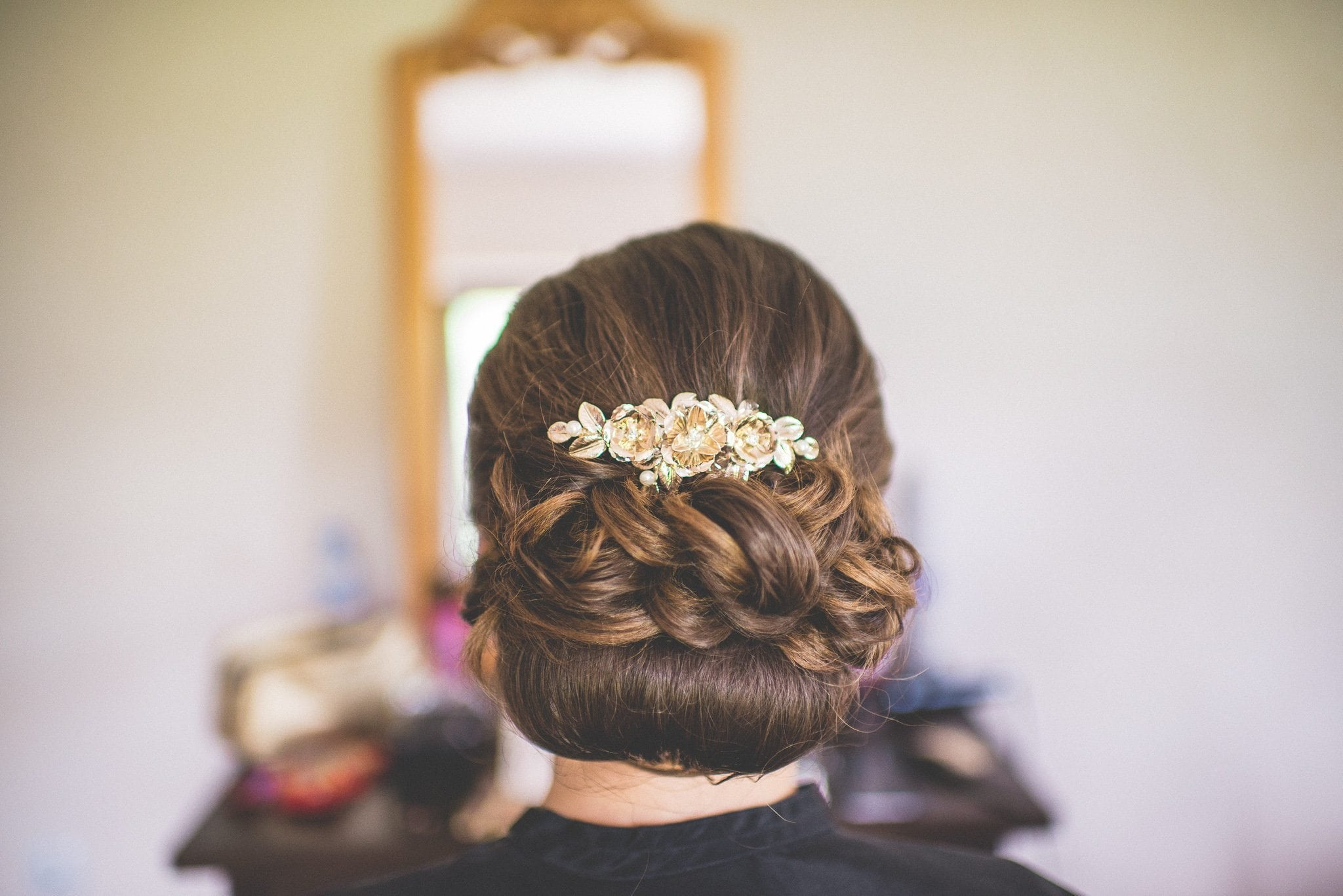 A shot of Elisaveta's finished hairstyle with a beautiful gold floral comb