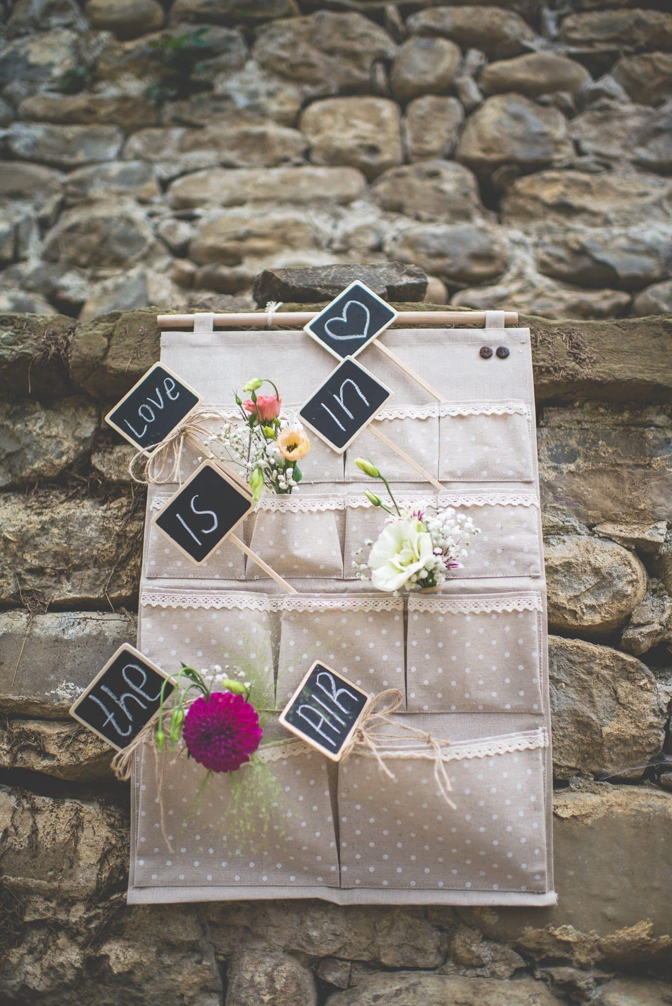 'Love is in the air' is written on individual chalkboard signs and placed in fabric pockets along with small posies of flowers