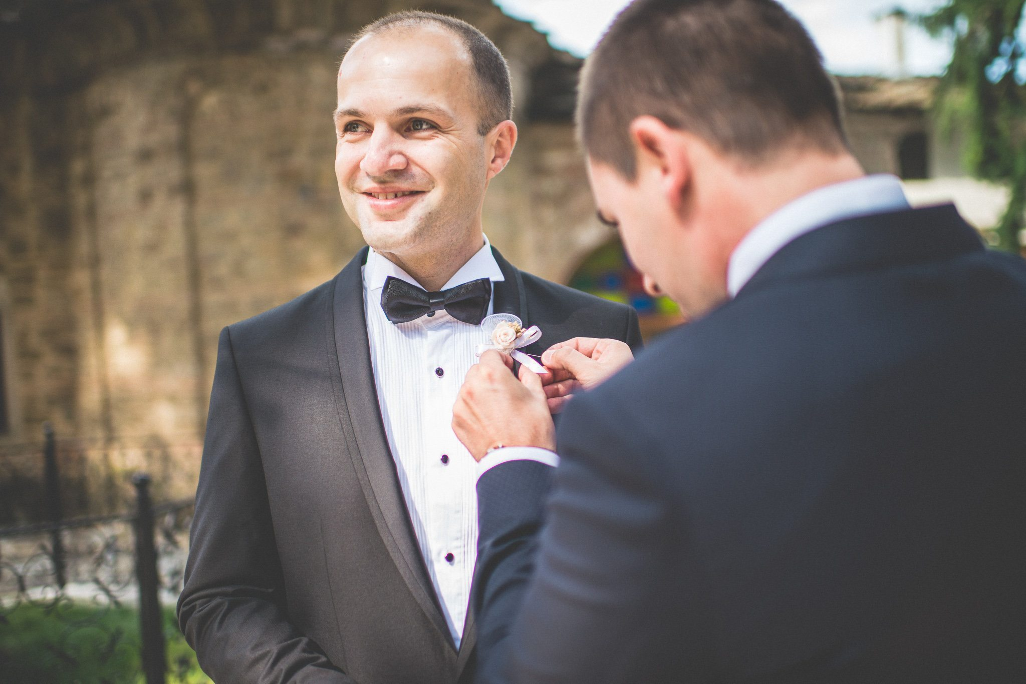 A groomsman pins on Martin's buttonhole