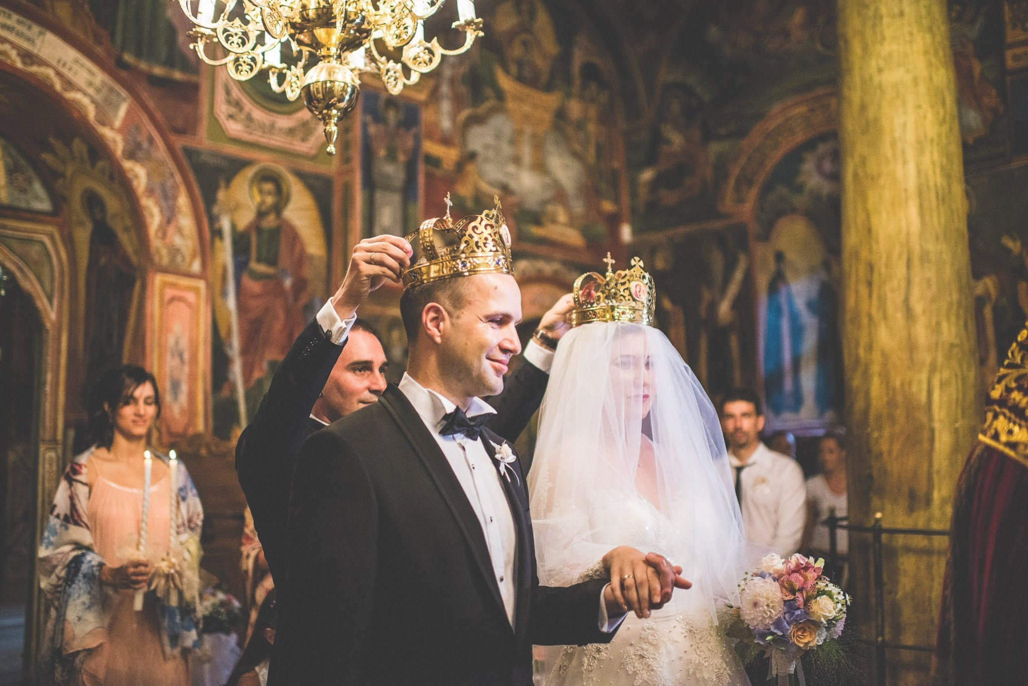 Ornate gold crowns are placed on the couple's heads during their Orthodox wedding ceremony