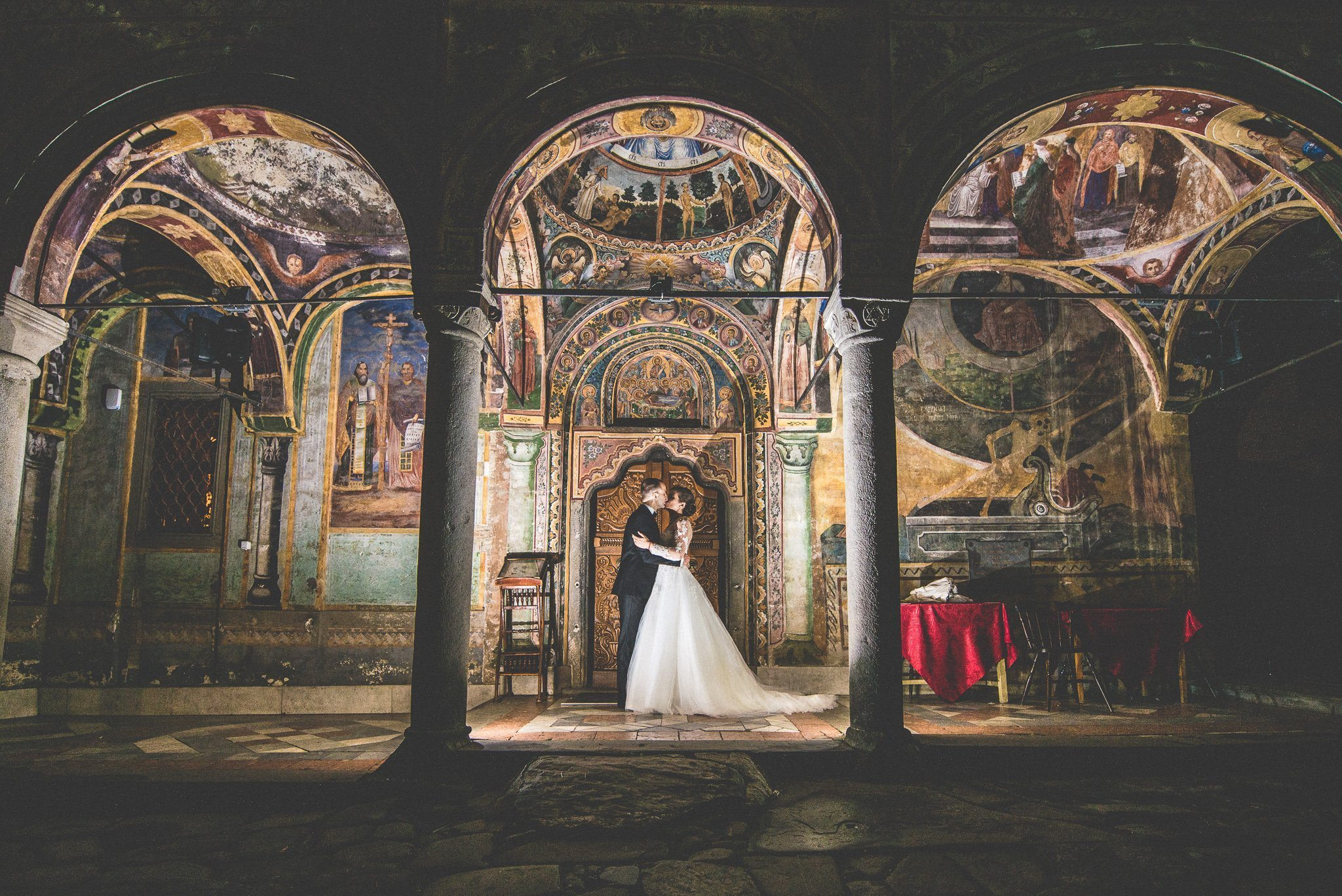 Martin and Elisaveta kiss under the arches of the monastery, among the hand painted frescoes which are lit at night