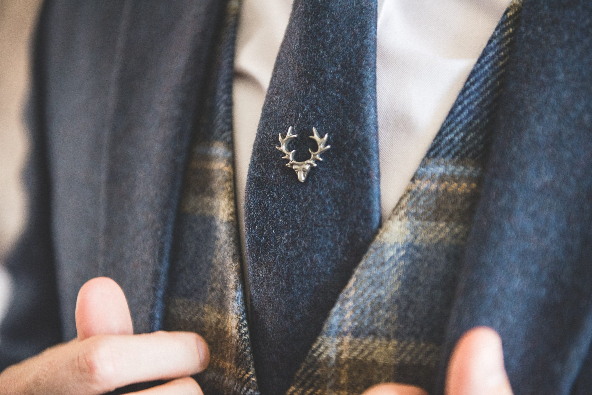 A close up of the silver stag pin on Philip's blue woollen tie