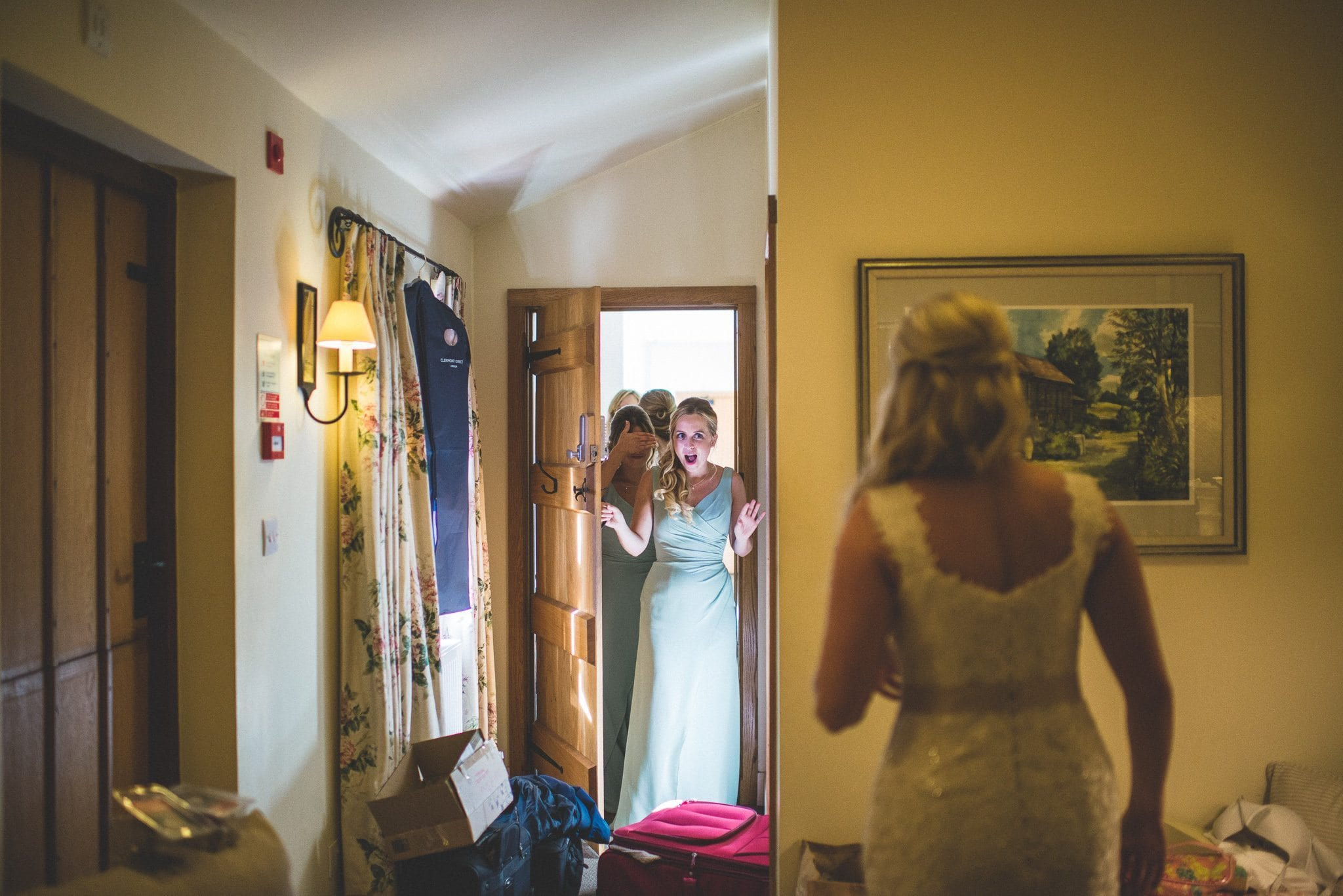 Emma is seen from behind as the bridesmaids enter the room and see her in her dress for the first time