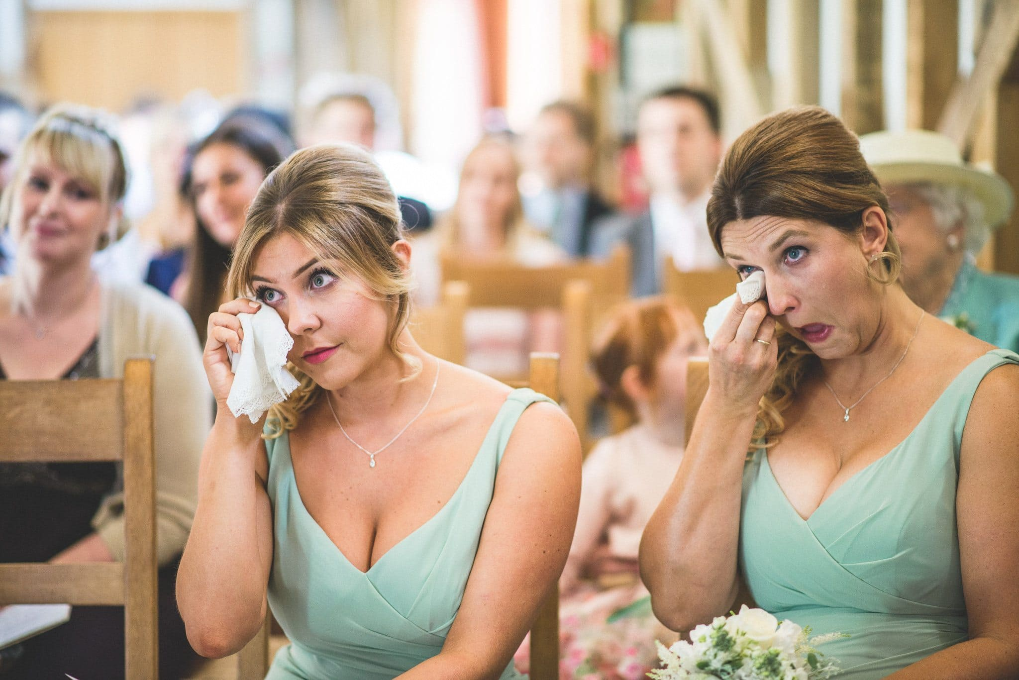 Two of the bridesmaids, wearing mint green dresses, simultaneously wipe tears from their eyes during the ceremony