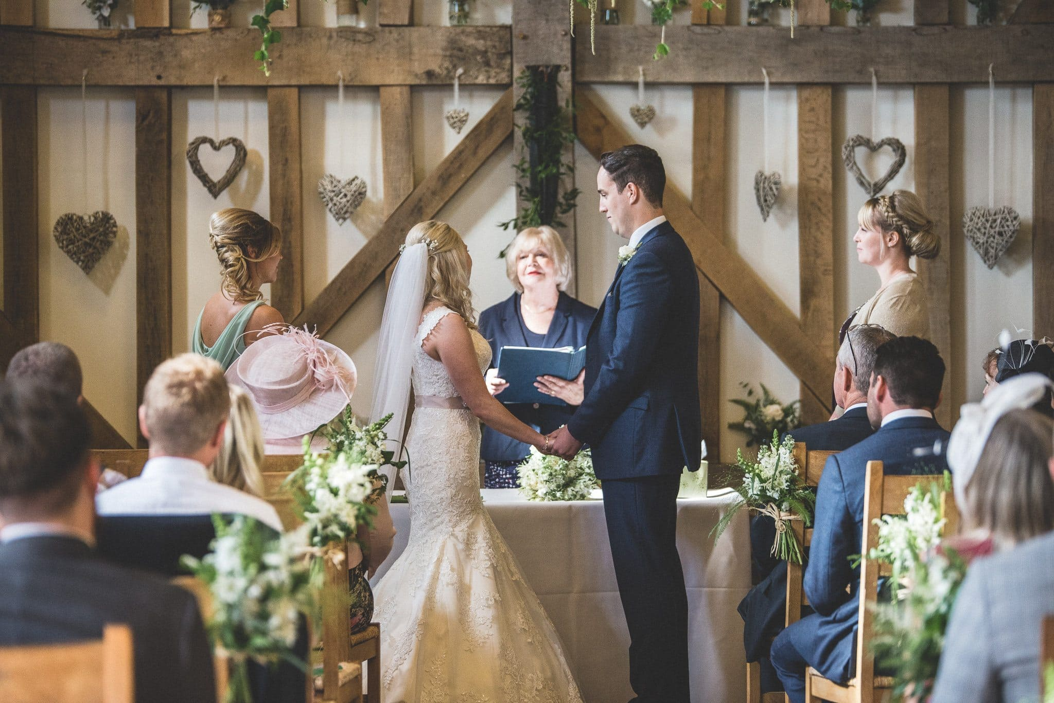 Emma and Philip hold hands at the end of the aisle as the registrar conducts their marriage ceremony
