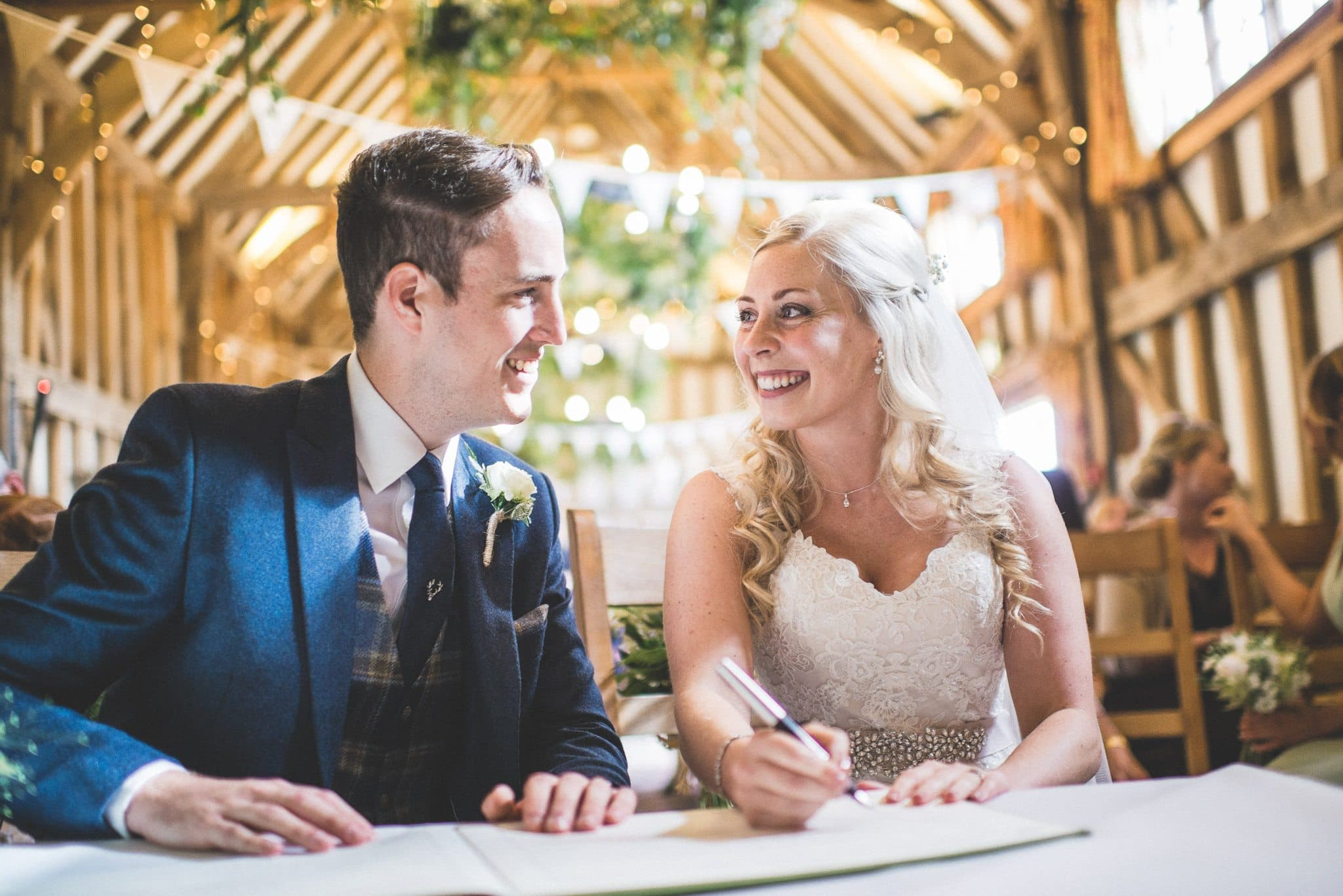 The newlyweds smile happily as they sign the register