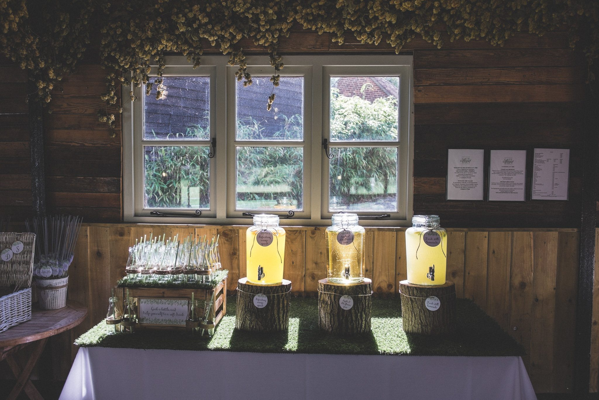 Glass drinks dispensers rest on large log slices as the sun streams through a window.