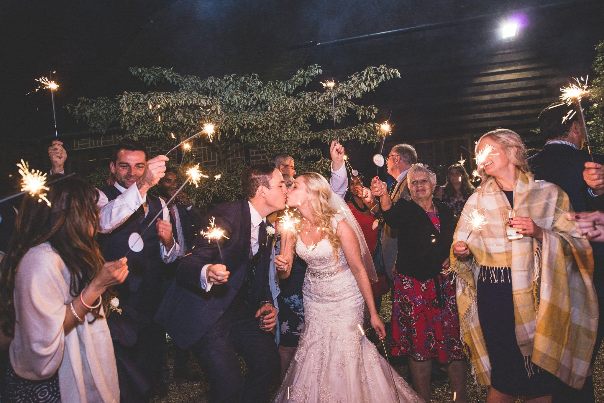 Emma and Philip kiss as guests wave their sparklers