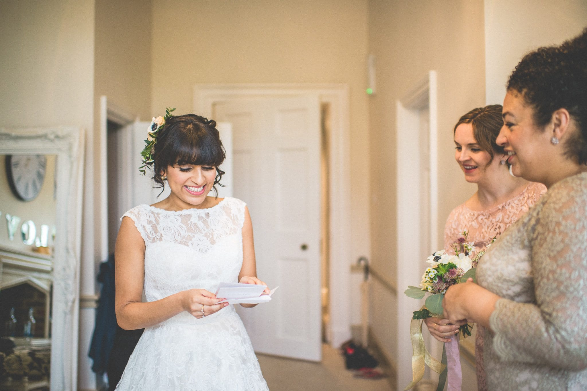 Jasmin smiles while reading a message from her groom as two of her bridesmaids look on