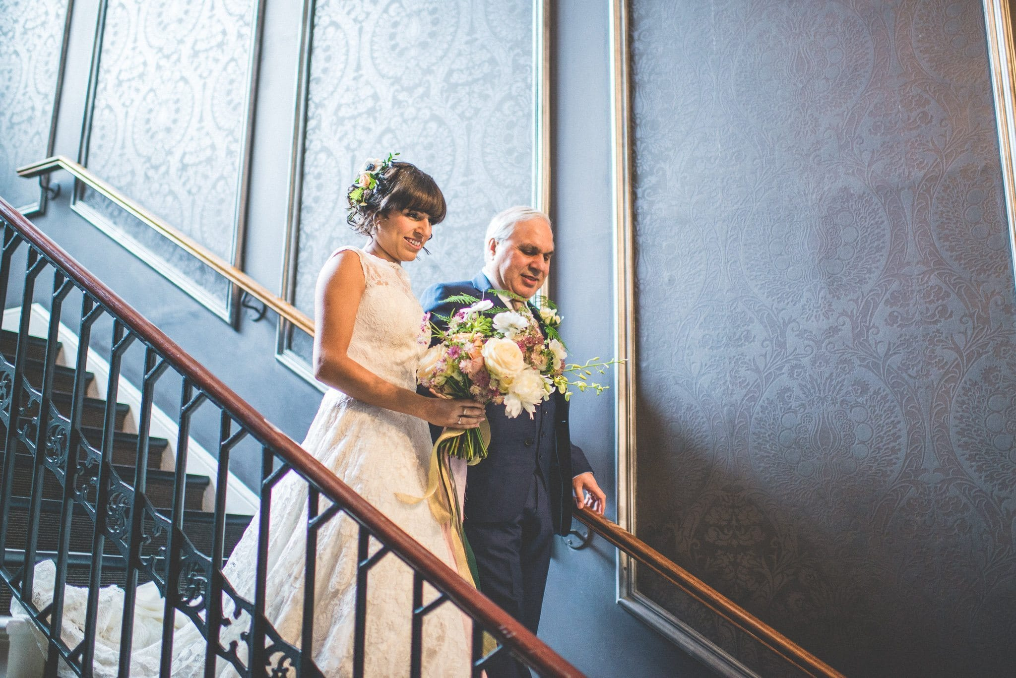 The bride descends the staircase to the ceremony room at Nonsuch Mansion