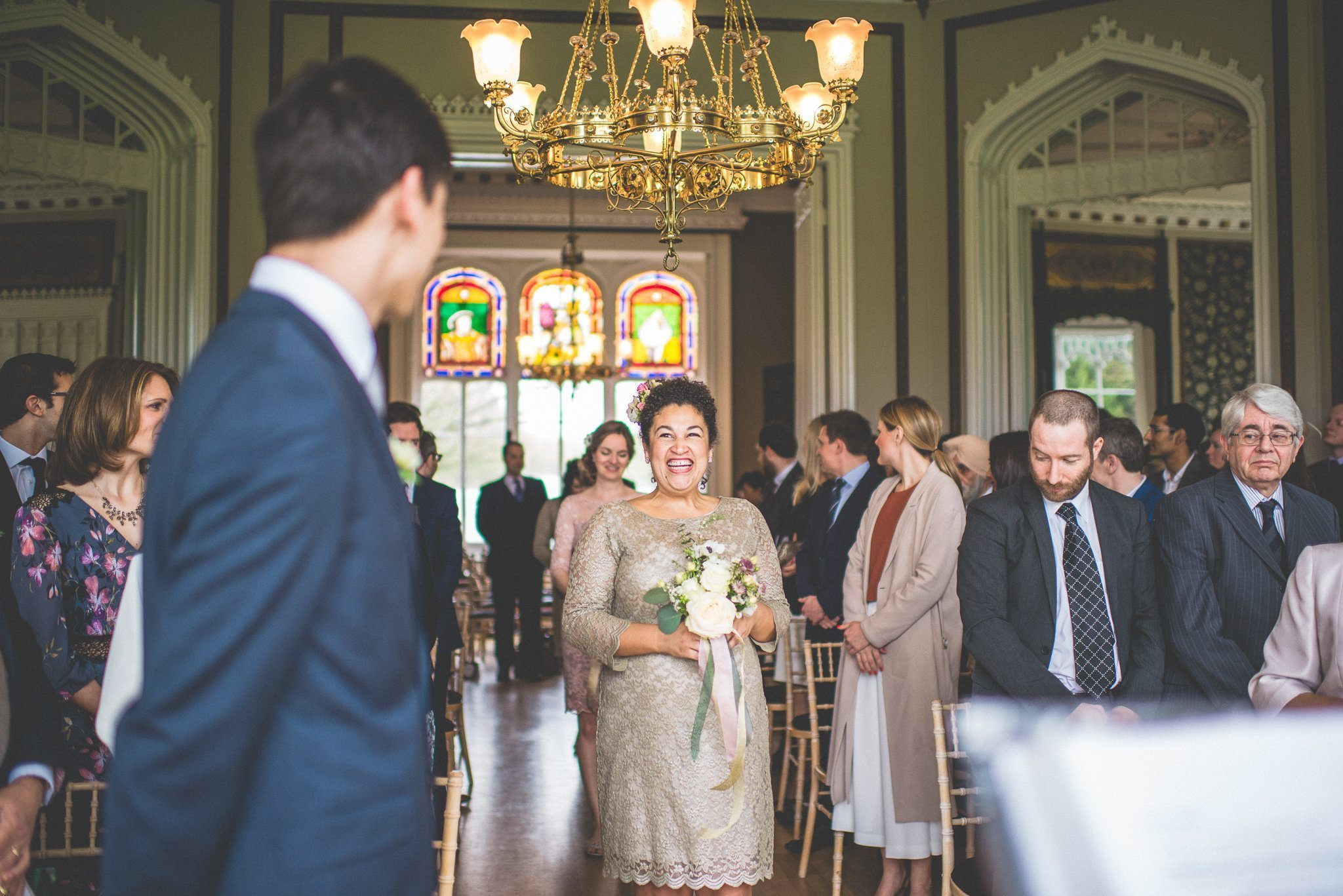 The bridesmaids walk down the aisle, carrying posies and wearing dresses in gold and pale pink