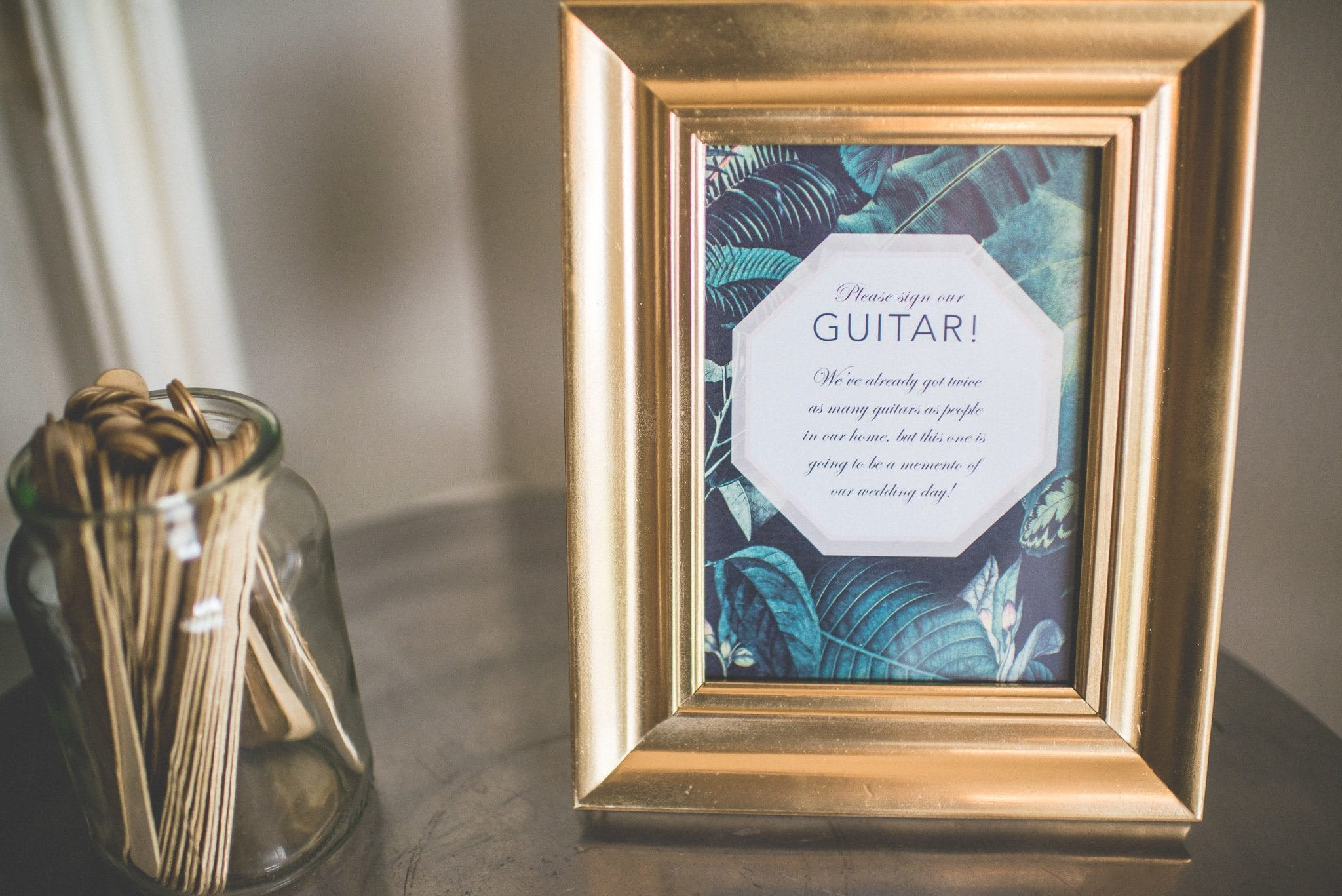 A framed instruction for guests - Sign Our Guitar! - shows Jasmin and Andy's musical take on a guestbook