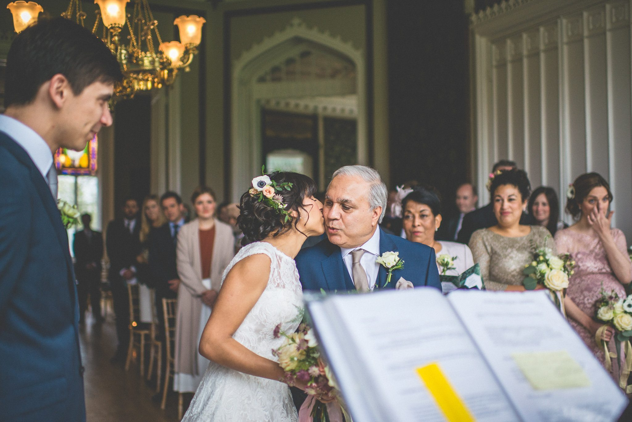 Jasmin kisses her father on the cheek as her groom looks on