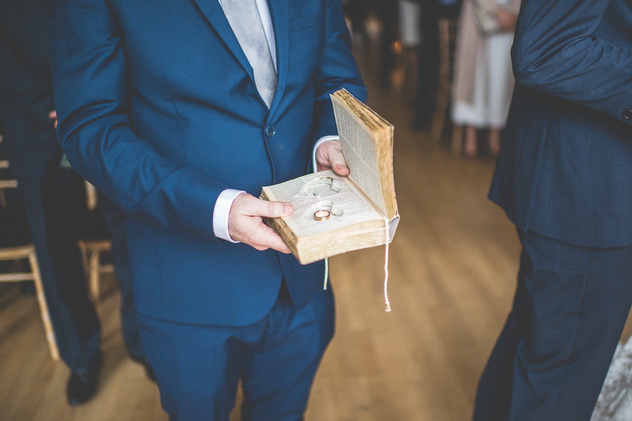 A close up of the wedding rings, which are carried inside a book with hearts cut into the pages