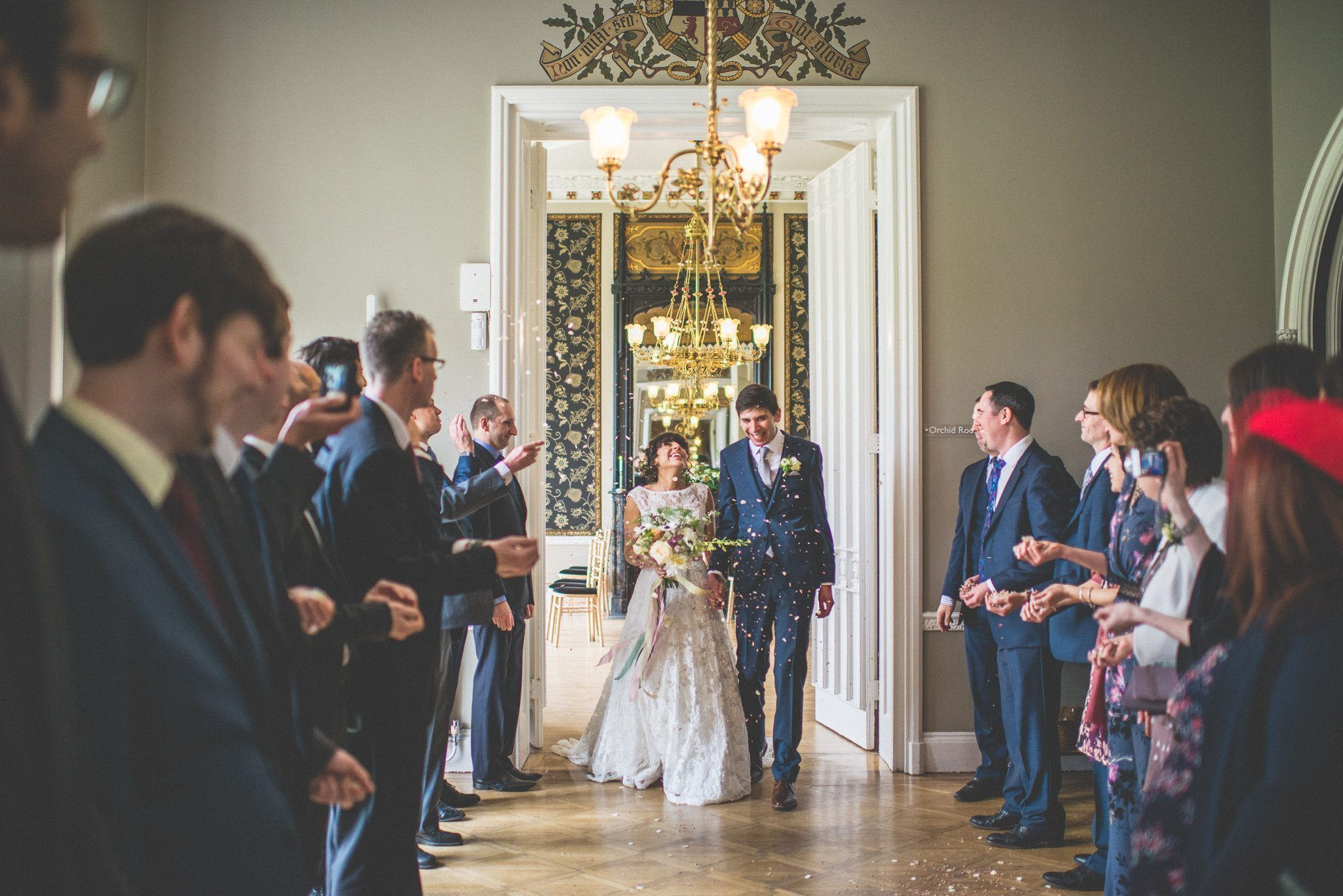 The couple emerge from the ceremony room in a shower of petal confetti