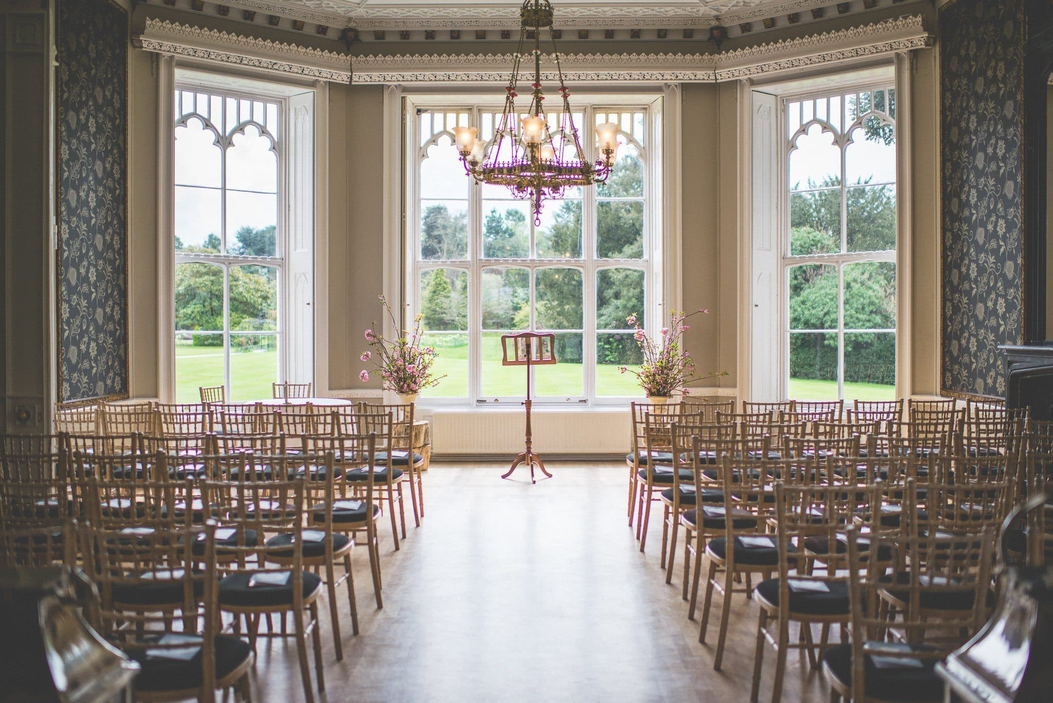 A view into the empty ceremony room at Nonsuch Mansion, with a large floor-to-ceiling bay window and chandelier with pink and gold details.