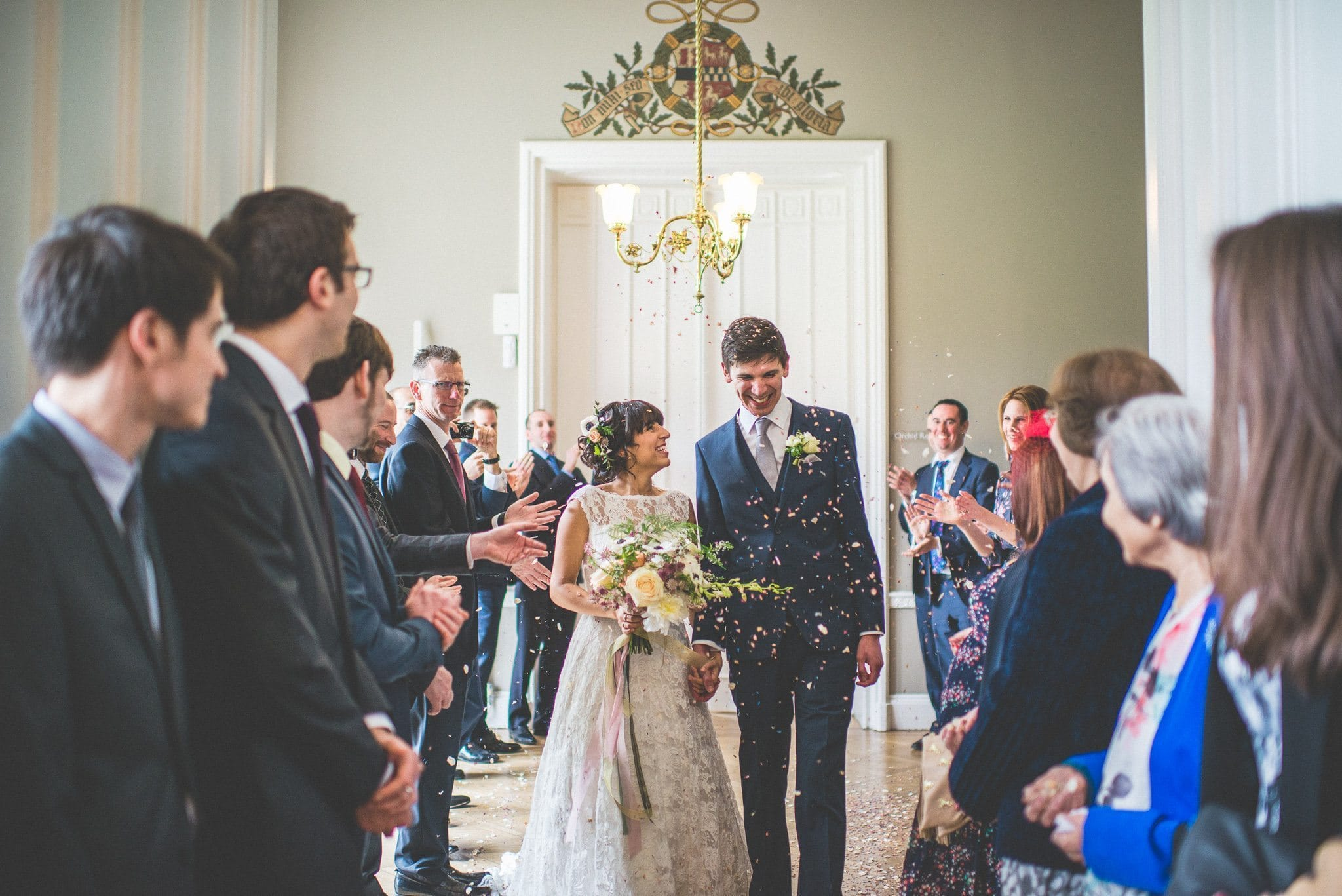 Jasmin looks lovingly at Andy as they walk through their guests and confetti is thrown