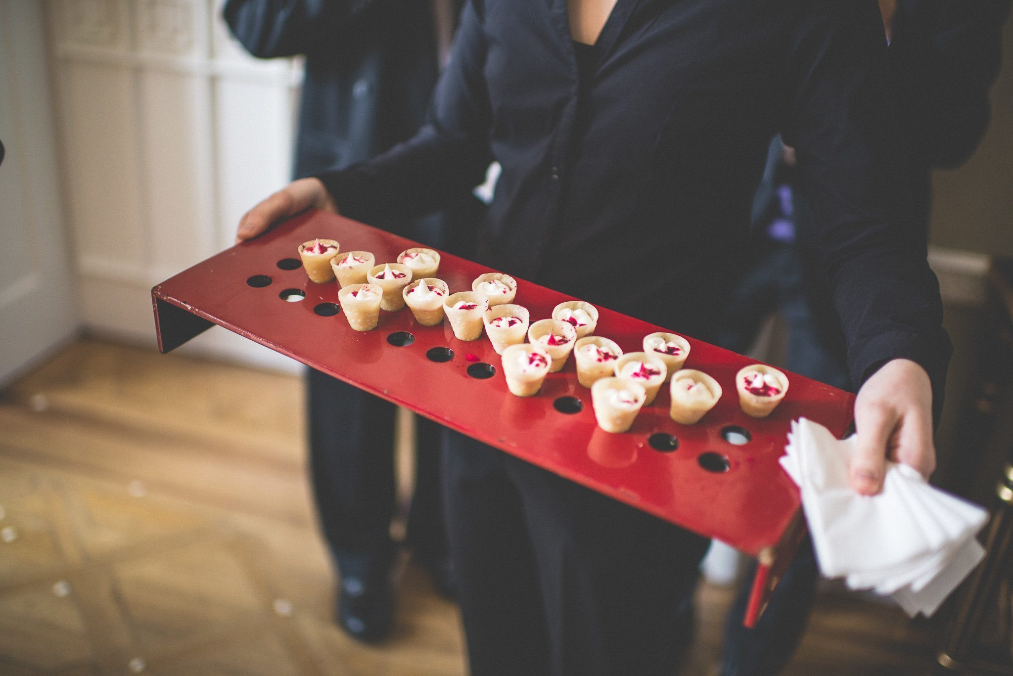 A close up of some of the mini canape cones, served on a red tray
