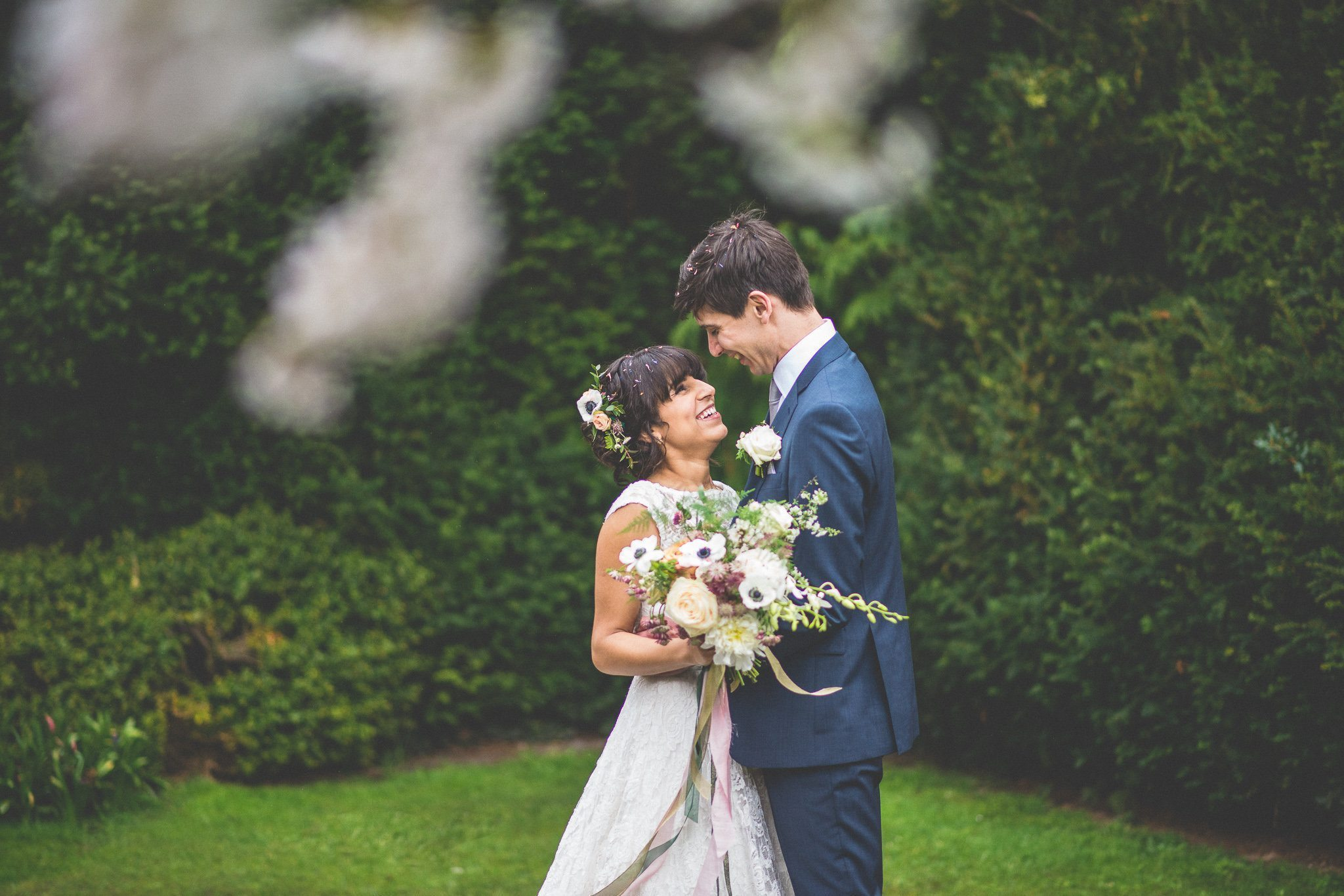 The couple go outside for their couple's portraits. Here, they are pictured through the branches of a blossom tree, looking lovingly at each other with confetti petals in their hair.