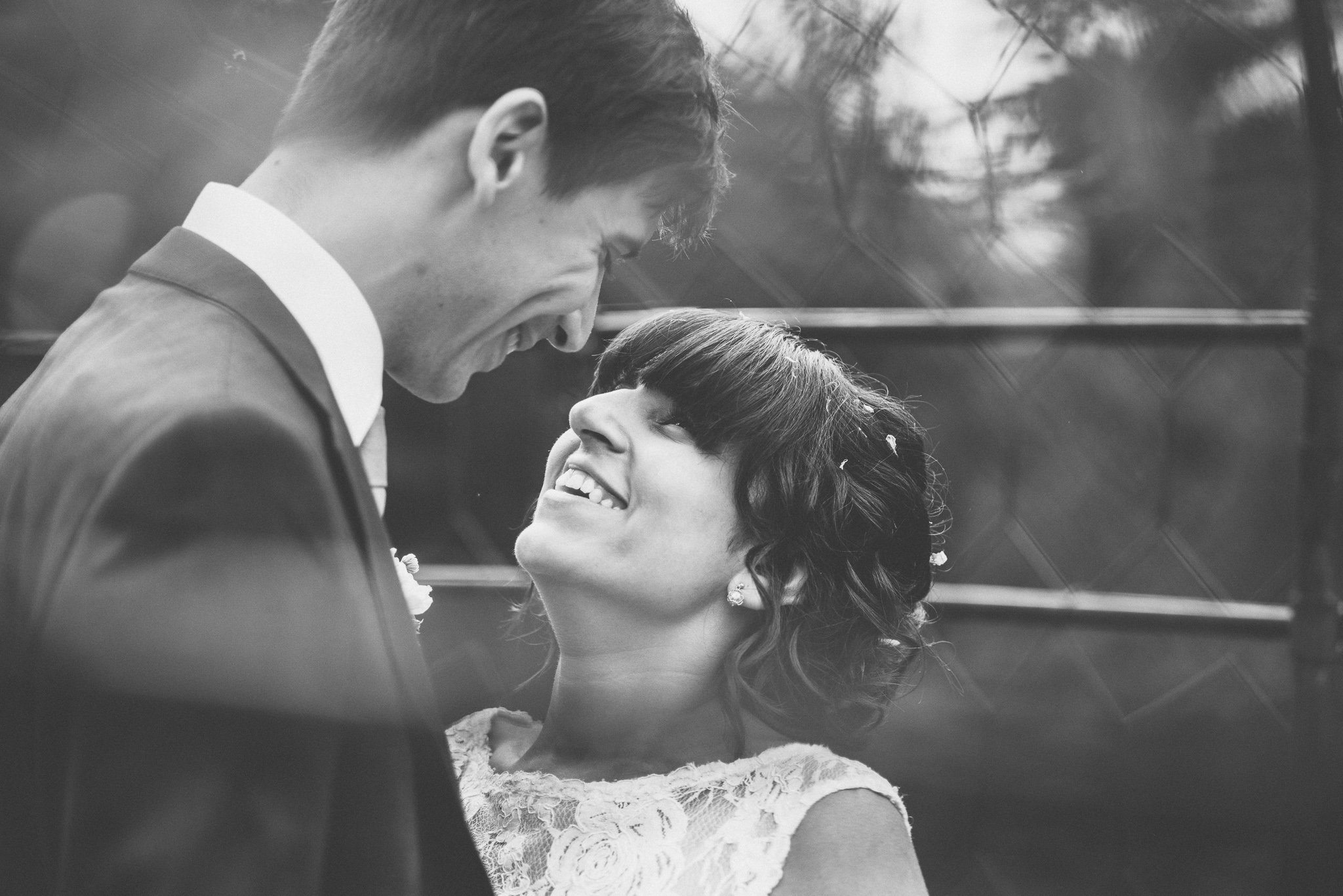 A black and white close up of the newlyweds smiling adoringly at each other
