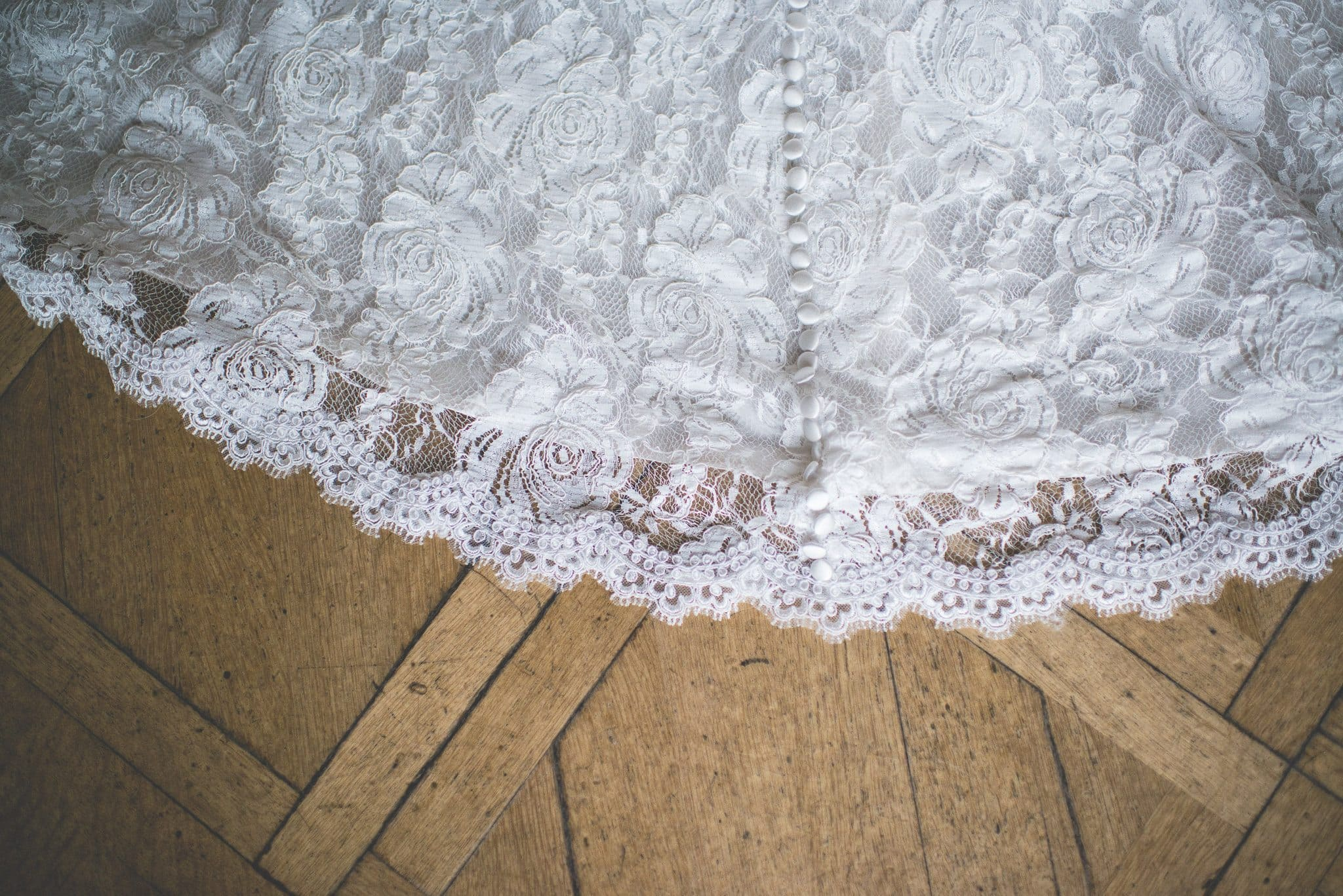 A close up shot of the lace detailing at the bottom of the wedding dress