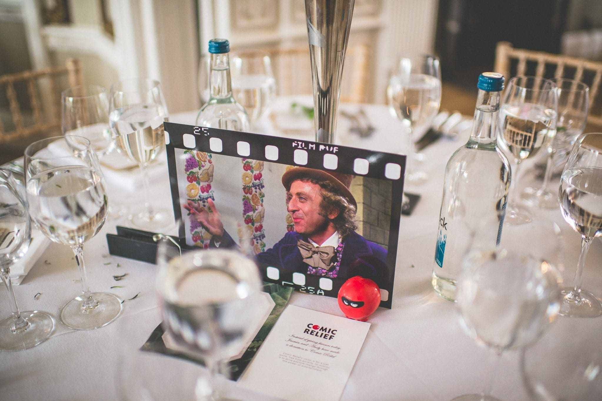 A close up of one of the film-themed table centres - showing Gene Wilder as Willy Wonka - and a note explaining that the couple have donated to Comic Relief in lieu of giving favours