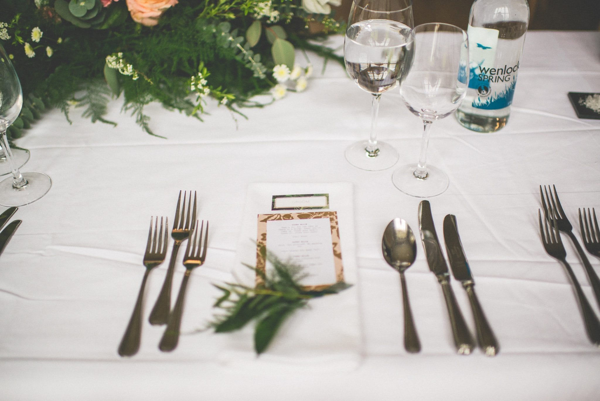 A close up of one of the place settings, complete with fern